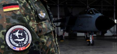 FILE PHOTO: A soldier of the German Armed Forces Bundeswehr wears a patch of the combat wing Counter DAESH Incirlik next to a German Tornado jet in a hangar before a statement of the German and Turkish defence ministers at the air base in Incirlik