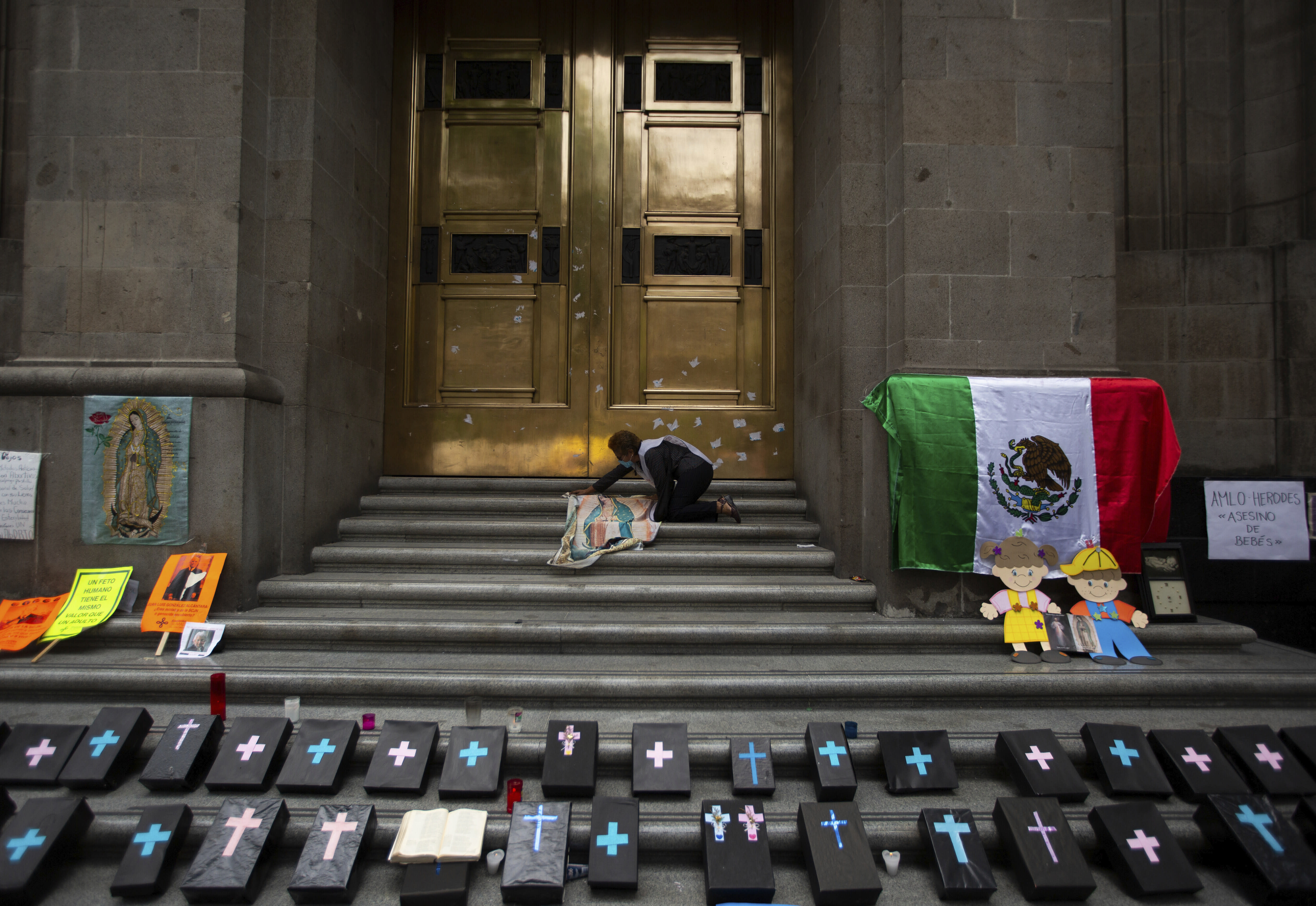 An activist against abortion places an image of Our Lady of Guadalupe alongside small, mock coffins at the entrance to the Supreme Court to celebrate the court's decision against an injunction in Veracruz state that aimed to decriminalize abortion for all cases within the first 12 weeks of pregnancy, in Mexico City, Wednesday, July 29, 2020. Two of Mexico's 32 states have decriminalized abortion. (AP Photo/Fernando Llano)