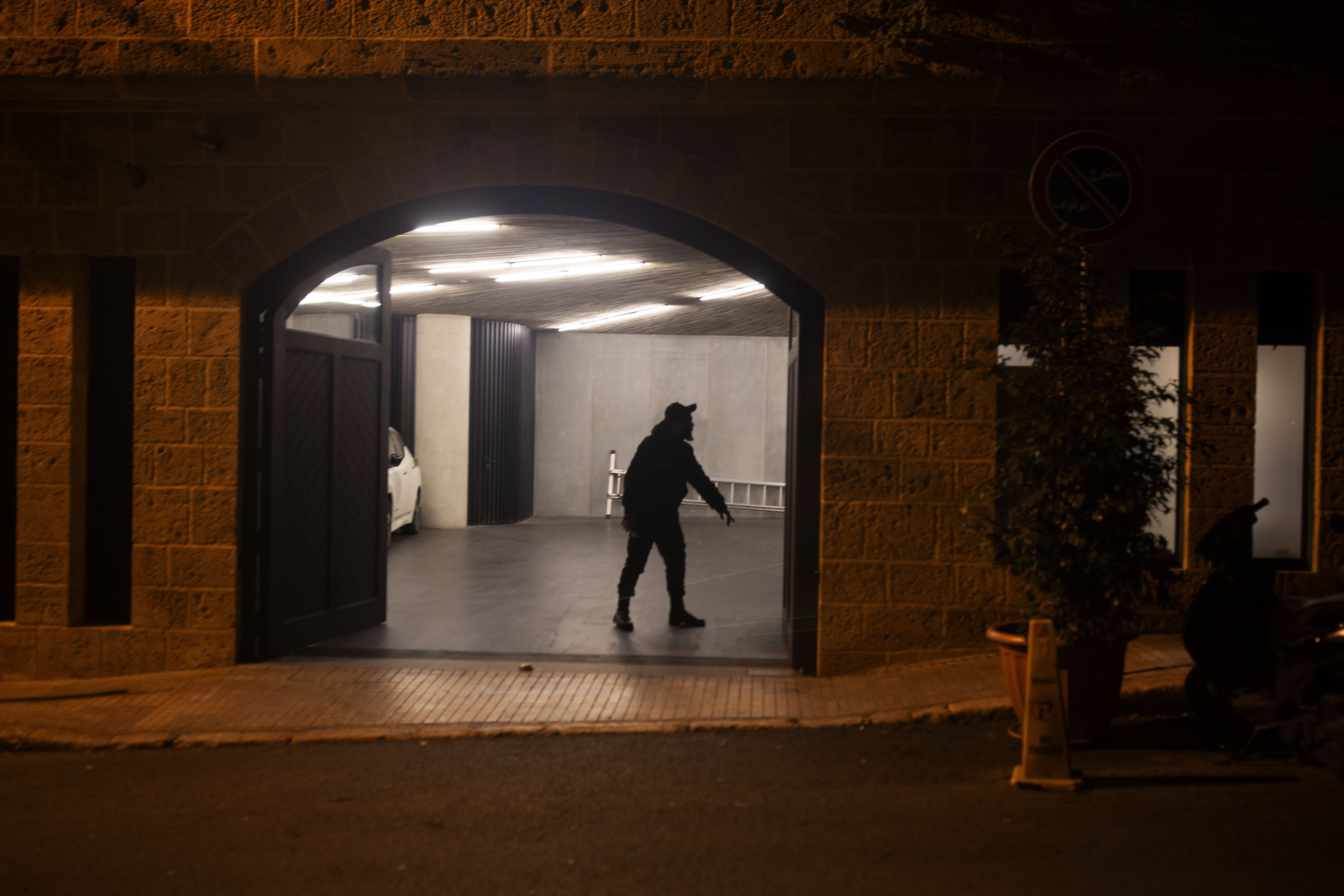 A security guard stands in the garage at the residence of former Nissan Chairman Carlos Ghosn on Monday, Dec. 30, 2019 in Beirut, Lebanon. A close friend says Ghosn, who is awaiting trial in Japan, has arrived in Beirut. It was not clear how Ghosn, who is of Lebanese origins, left Japan where he is under surveillance and is expected to face trial in April 2020. (AP Photo/Maya Alleruzzo)