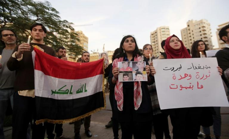 """Lebanese protesters at the vigil carry the Iraqi national flag and a poster reading """"From Baghdad to Beirut, one revolution that will not die"""" (AFP Photo/ANWAR AMRO)"""