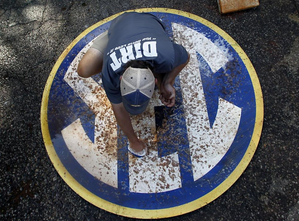In this May 23, 2014 photo, John Wagnon, of Florida, cleans the SEC logo before a game at the Southeastern Conference NCAA college baseball tournament in Hoover, Ala. A 40-man grounds crew labored to keep Hoover Met's field in good shape for the six-day, 17-game tournament