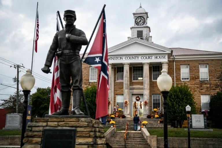 A Confederate flag and a US flag are seen near a Civil War memorial as Republican Party supporters arrive for a meeting at the Winston County courthouse in Alabama on October 12, 2020