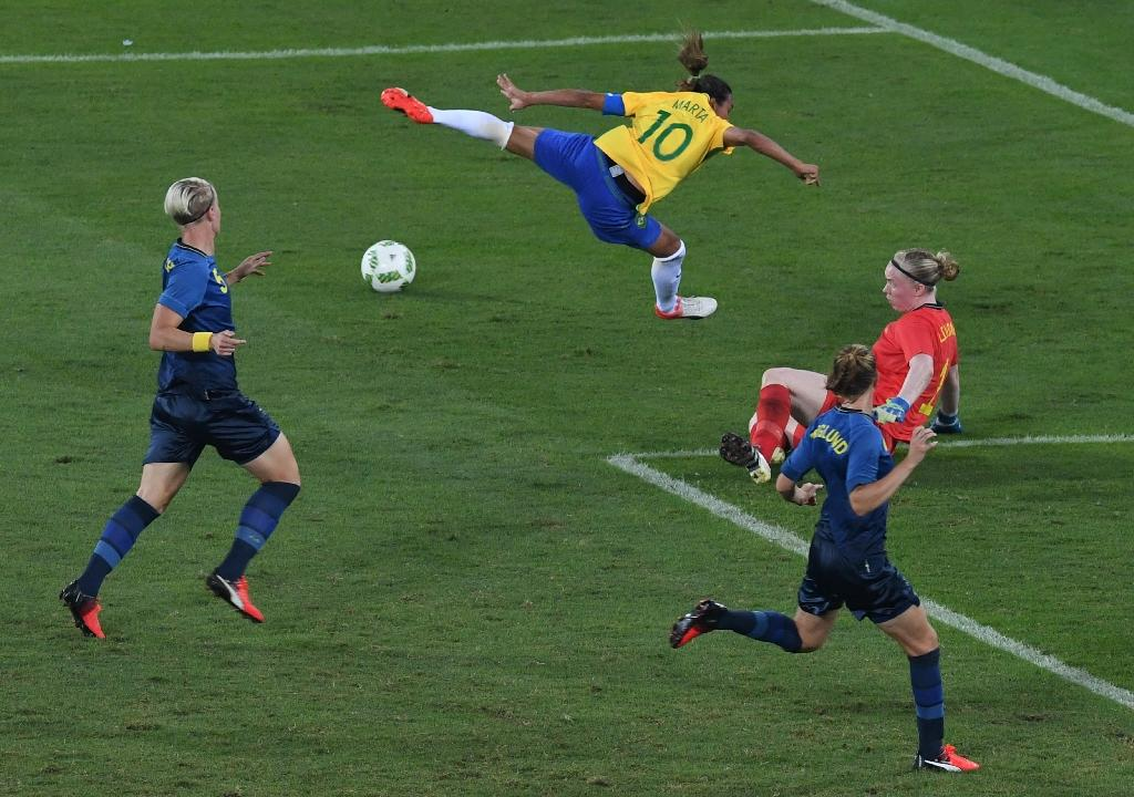 Brazil's player Marta (top) tries to score past Sweden's goalkeeper Lindahl Hedvig during the Rio 2016 Olympic Games Women's First Round Group E football match (AFP Photo/Vanderlei Almeida)