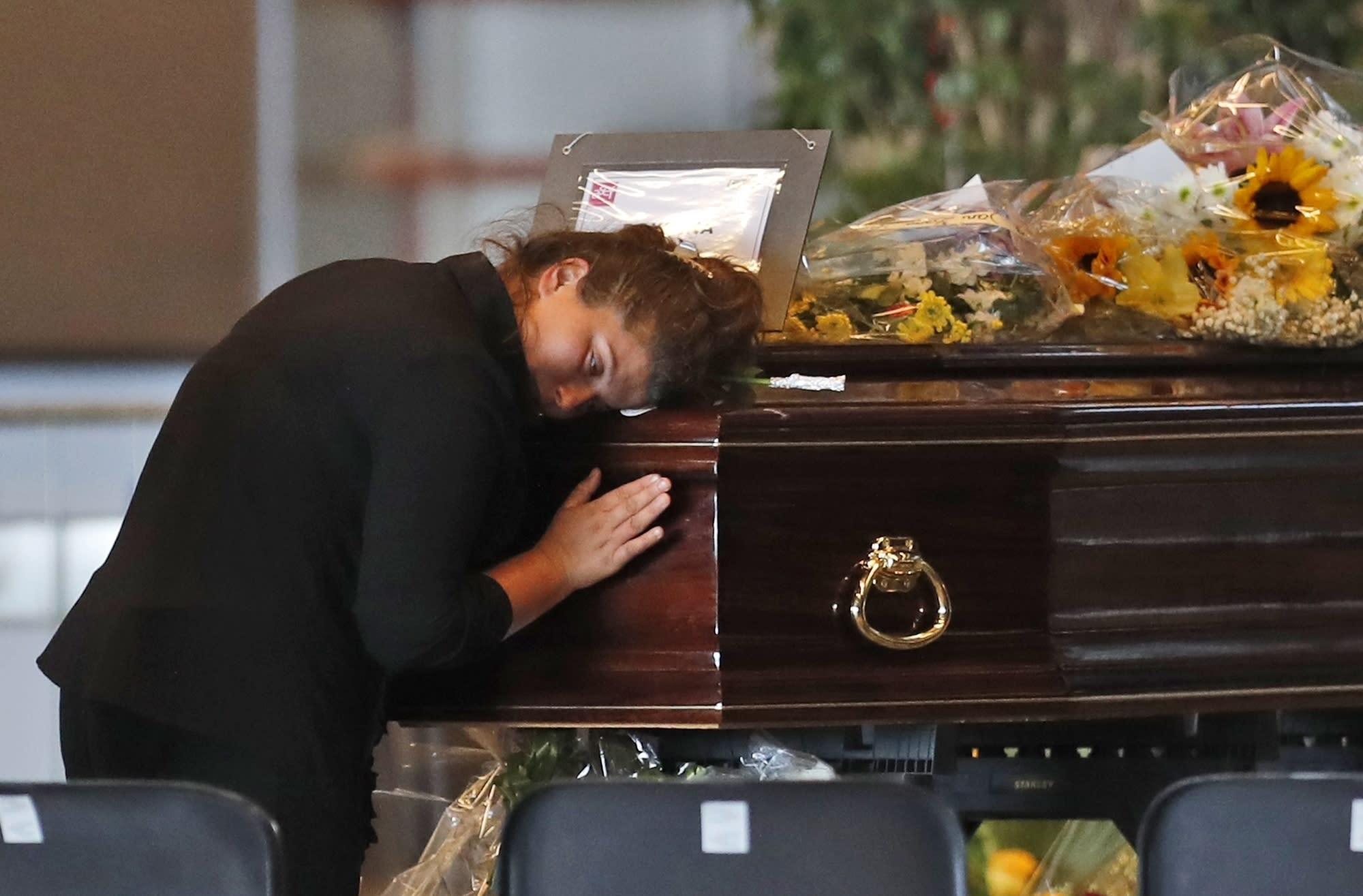 A woman mourns a victim of a collapsed highway bridge, at the Fiera di Genova exhibition center, where some of the coffins are laid in state, in Genoa, Italy, Friday, Aug. 17, 2018. A state funeral for most of the victims will take place in Genoa on Saturday. (AP Photo/Antonio Calanni)