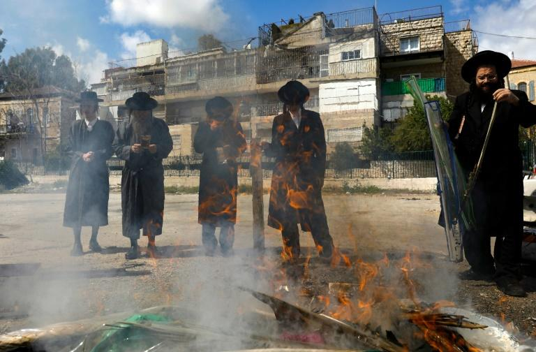 Jewish men burn food with leavening agents ahead of the start of Passover, in the the ultra-Orthodox Mea Shearim neighbourhood of Jerusalem (AFP Photo/MENAHEM KAHANA)