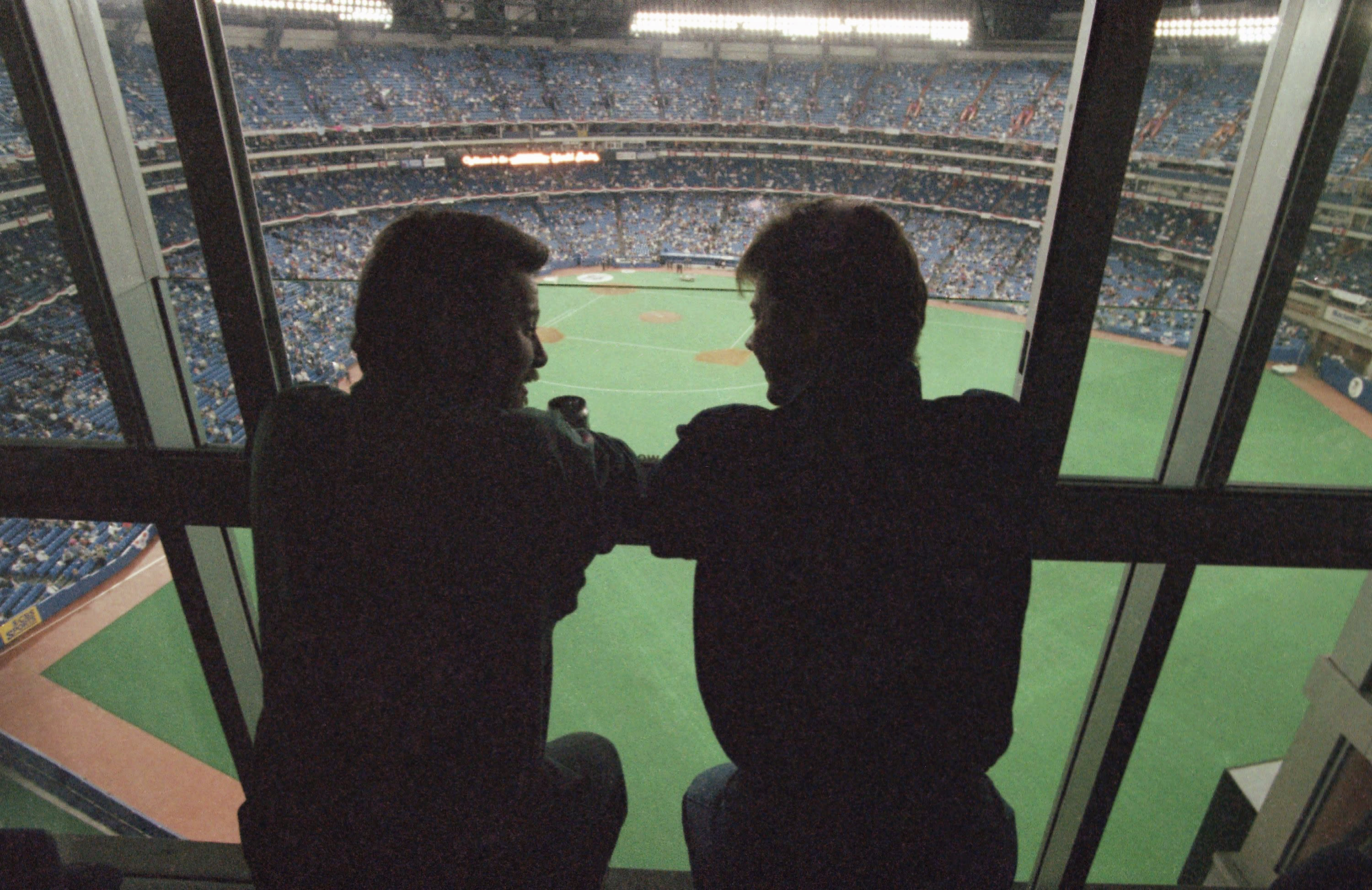 FILE - In this Oct. 22, 1992, file photo, spectators look out at the field from a window of the SkyDome Hotel before Game 5 of the World Series between the Toronto Blue Jays and the Atlanta Braves in Toronto. All 30 Major League Baseball teams will train at their regular-season ballparks for the pandemic-shortened season after the Blue Jays received a Canadian federal government exemption on Thursday, July 2, 2020, to work out at Rogers Centre. Toronto will move camp from its spring training complex in Dunedin, Fla., where players reported for intake testing. The Blue Jays will create a quarantine environment at Rogers Centre and the adjoining Toronto Marriott City Centre Hotel, formerly the SkyDome, which overlooks the field. (AP Photo/Rusty Kennedy, File)