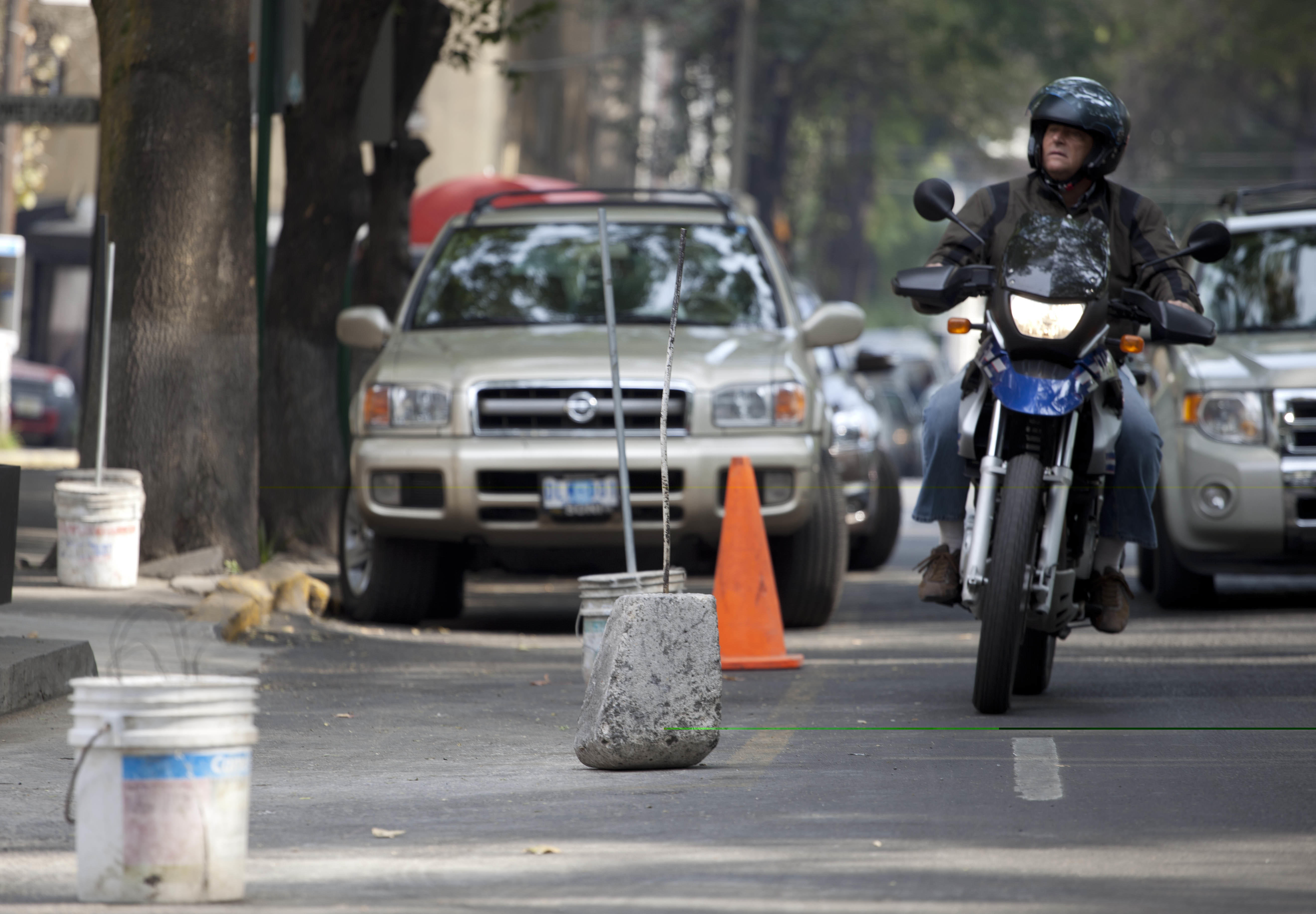 Cement blocks and buckets block off parking spaces along a street in the Condesa neighborhood of Mexico City, Friday, Jan. 18, 2013. Every day before dawn, dozens of men appear in the Mexican capital's hip Condesa neighborhood and block off parking spaces along entire streets using water jugs, cardboard boxes, buckets, crates and even blocks of cement. Here and in other well-to-do areas of traffic-choked Mexico City, authorities are trying to take back the streets by installing parking meters. On Sunday, Condesa's residents will decide in a referendum whether they want the meters on their streets. (AP Photo/Eduardo Verdugo)