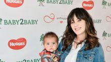 Zooey Deschanel poses with a super-cute baby on the red carpet, but it's not her super-cute baby