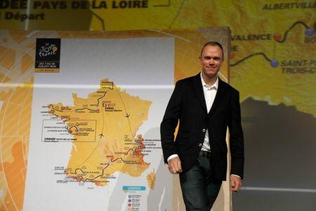 Tour de France 2017 winner Chris Froome of Britain poses with map of the itinerary of the 2018 Tour de France cycling race during a news conference in Paris, France