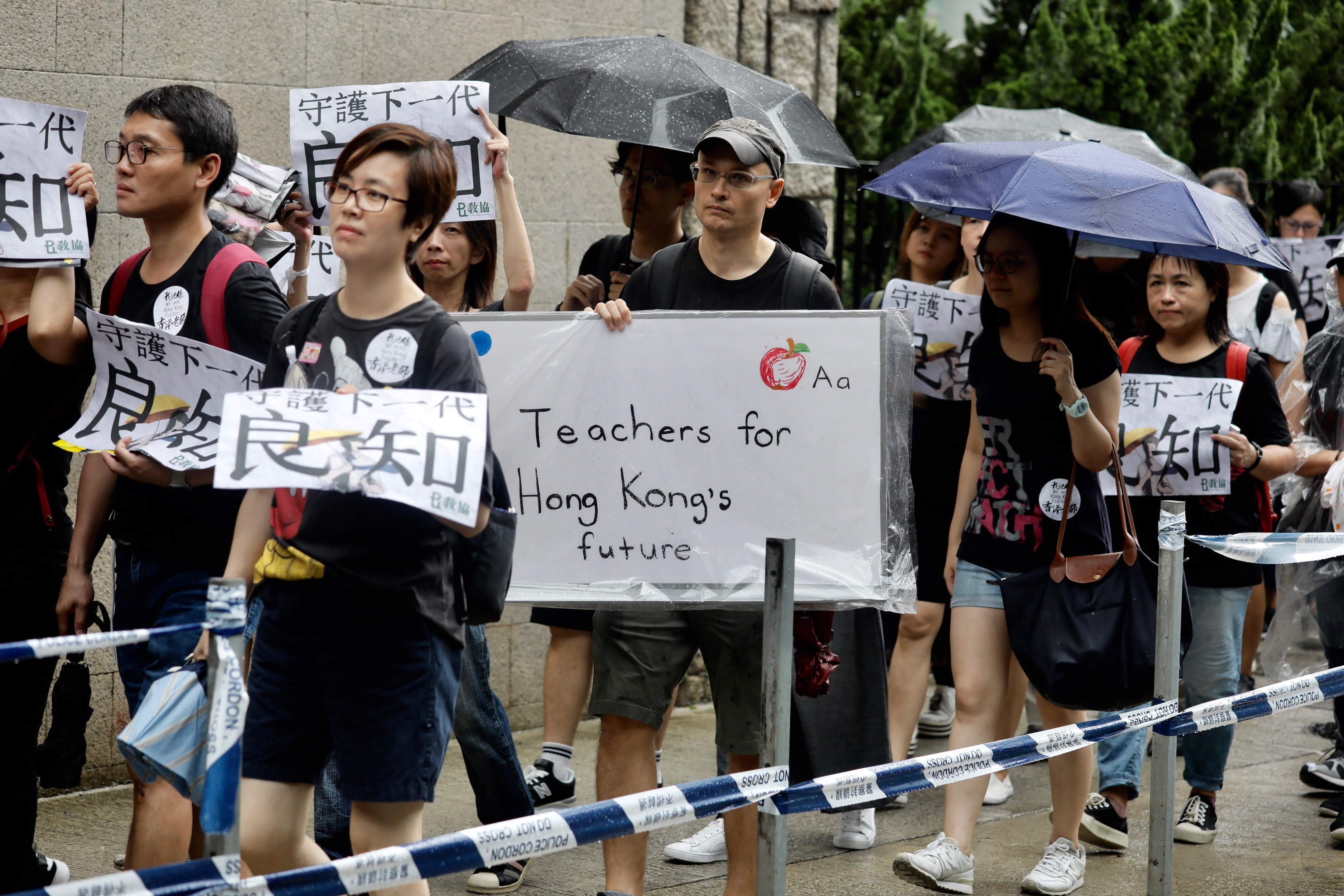 Pro-democracy protesters march organized by teachers in Hong Kong Saturday, Aug. 17, 2019. Members of China's paramilitary People's Armed Police marched and practiced crowd control tactics at a sports complex in Shenzhen across from Hong Kong in what some interpreted as a threat against pro-democracy protesters in the semi-autonomous territory. (AP Photo/Vincent Yu)