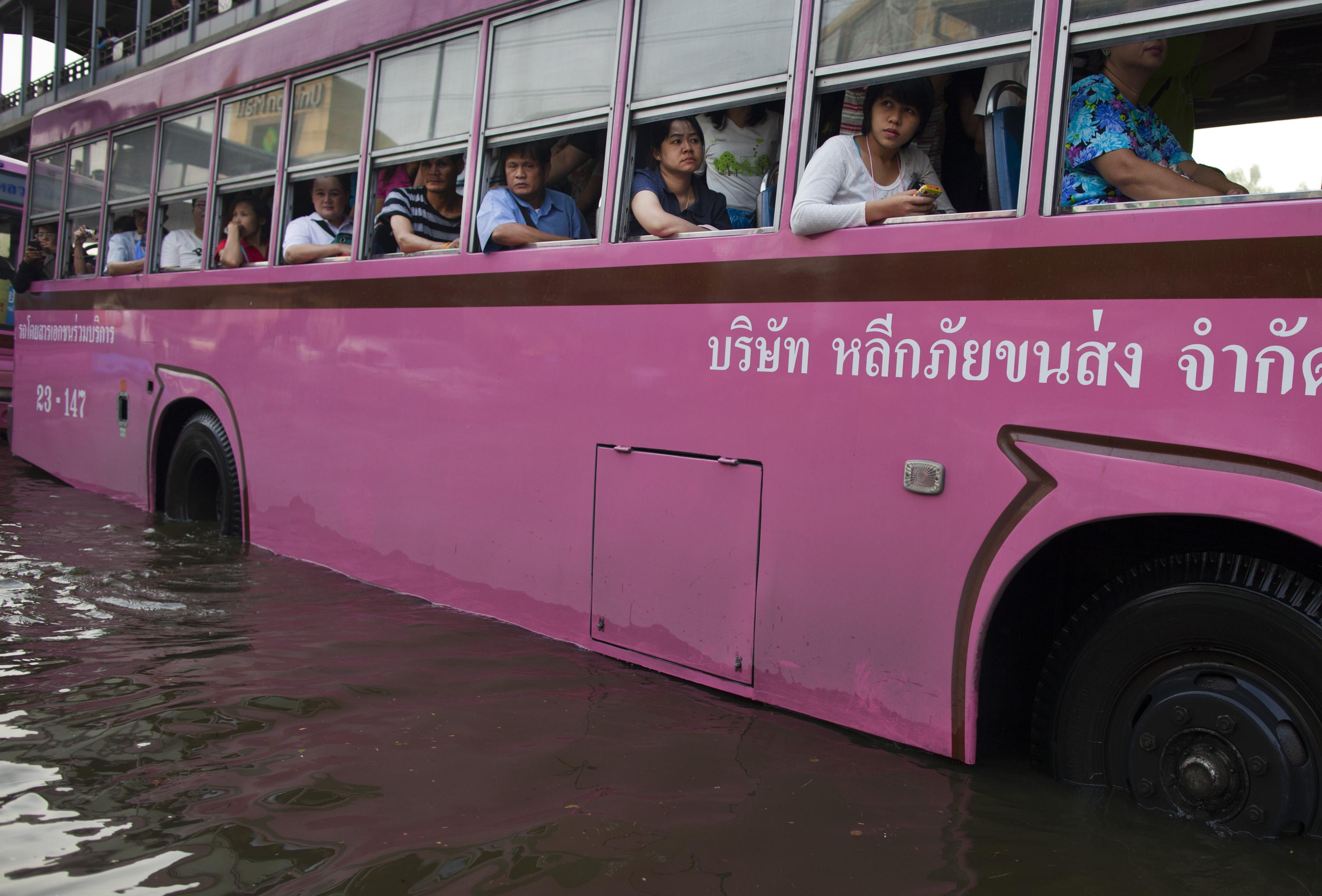 BANGKOK,THAILAND - NOVEMBER 4: A city bus take commuters home as flood waters take over the streets moving to the Lat Phrao area, a major shopping and business district November 4, 2011 in Bangkok, Thailand. Over seven major industrial parks in Bangkok and, thousands of factories have been closed in the central Thai province of Ayutthaya and Nonthaburi with millions of tons of rice damaged. Thailand is experiencing the worst flooding in over 50 years which has affected more than nine million people. Over 400 people have died in flood-related incidents since late July according to the Department of Disaster Prevention and Mitigation. (Photo by Paula Bronstein /Getty Images)