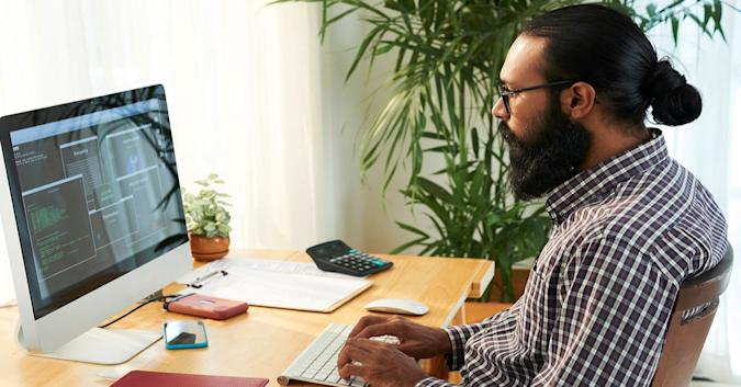 Stock image of a man in a checked button-down shirt using an all-in-one desktop.