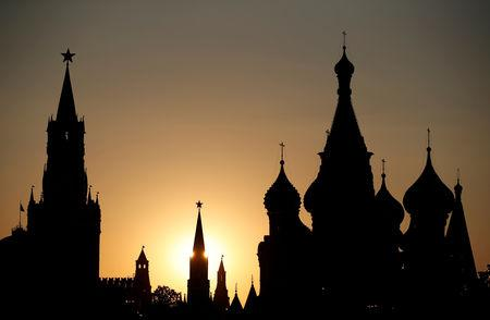 FILE PHOTO: The sun sets behind the Kremlin's Spasskaya Tower and St. Basil's Cathedral during the soccer World Cup in Moscow