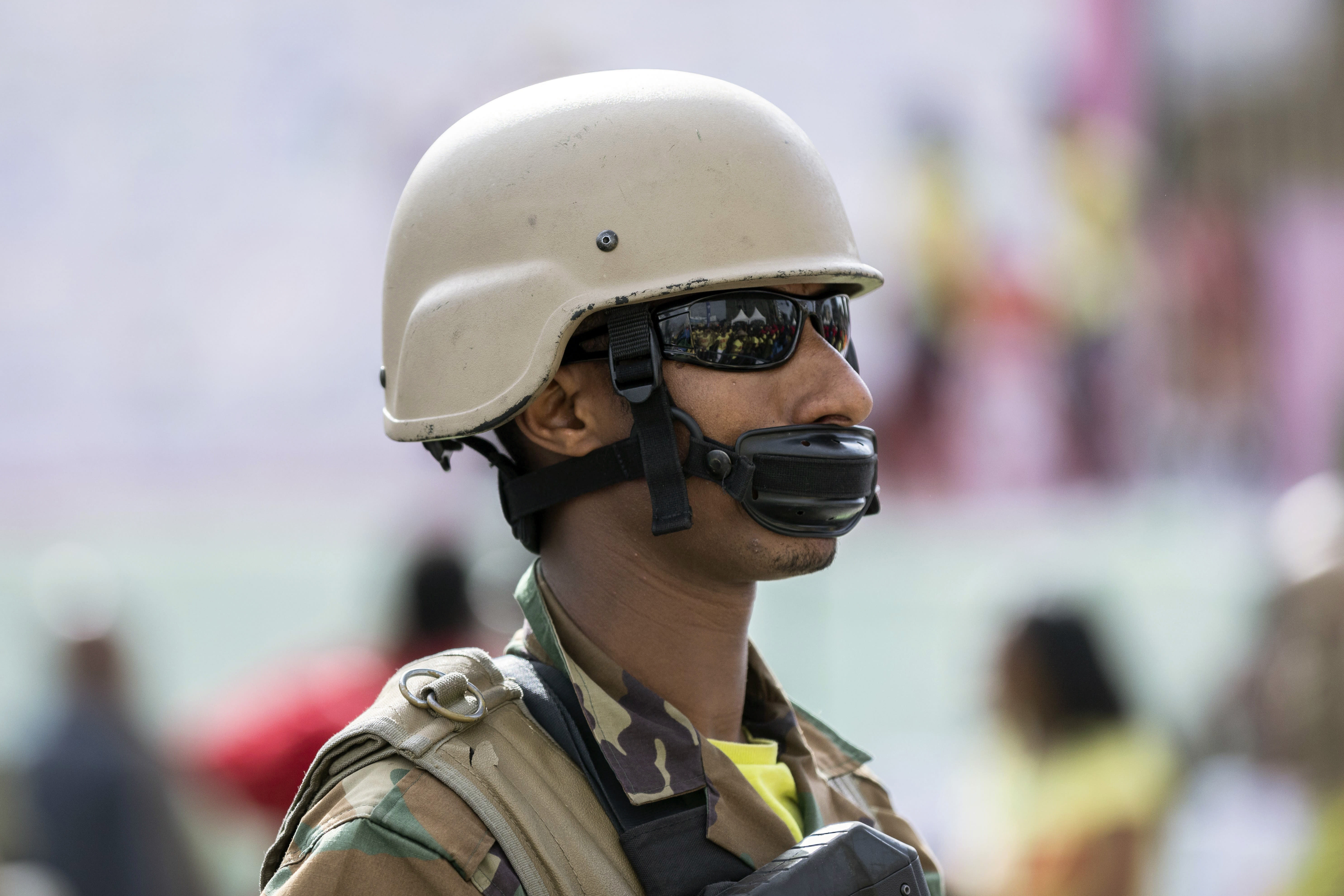 An Ethiopian soldier providing security during a visit by the president to a women's 5km fun run wears his chinstrap as a makeshift face mask to protect against the new coronavirus, in the capital Addis Ababa, Ethiopia Sunday, March 15, 2020. Ethiopia reported on Thursday its first case of the new coronavirus which causes COVID-19. For most people, the new coronavirus causes only mild or moderate symptoms, such as fever and cough but for some, especially older adults and people with existing health problems, it can cause more severe illness, including pneumonia. (AP Photo/Mulugeta Ayene)