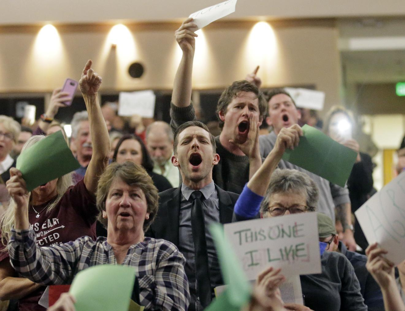People shout to Rep. Jason Chaffetz during his town hall meeting at Brighton High School Thursday, Feb. 9, 2017, in Cottonwood Heights, Utah. Hundreds of people lined up early for a town hall with Chaffetz on Thursday evening, many holding signs criticizing the congressman's push to repeal the newly-named Bears Ears National Monument in southern Utah. (AP Photo/Rick Bowmer)