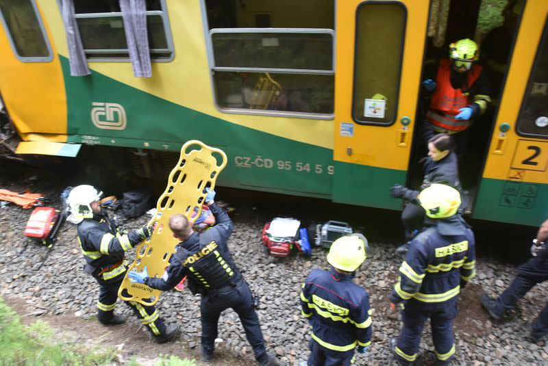 Firefighters are seen working on a site of a train crash near Pernink