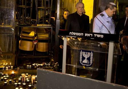Israeli Prime Minister Benjamin Netanyahu walks with police commissioner Roni Alsheich during a visit to the scene of a shooting incident in Tel Aviv, Israel