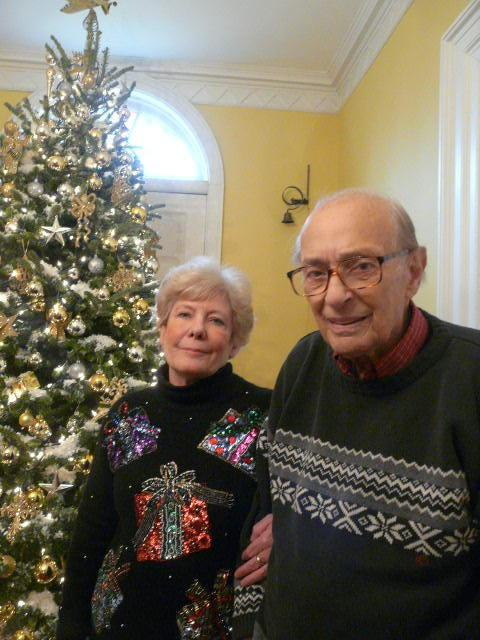 "<p>Peter and Sandra Mollica, decked out in the Christmas gear in front of their own tree. Sandra Mollica says that the Fraser fir trees on the farm rarely shed their needles, and to prove it, she displayed the same tree for three years. ""Eventually it got brown, but it didn't shed those needles,"" she says. <i>(Photo courtesy Sandra Mollica)</i><br></p>"