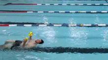 Man juggles balls while swimming backwards
