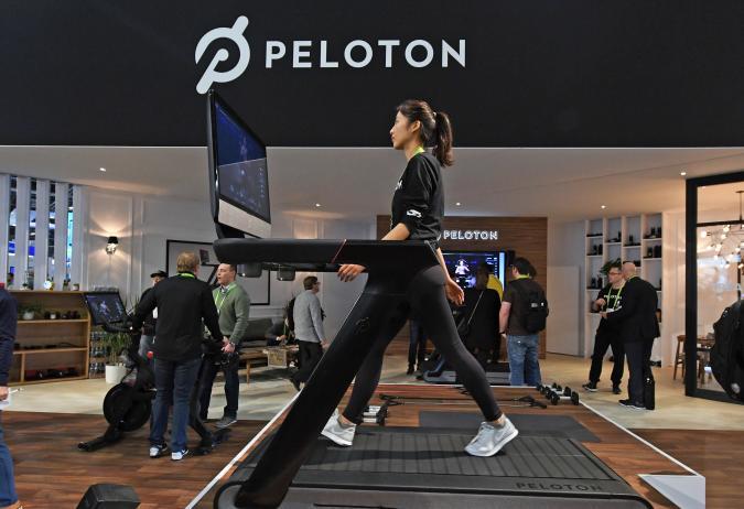 A woman walks on a Peloton treadmill in the Peloton showroom.