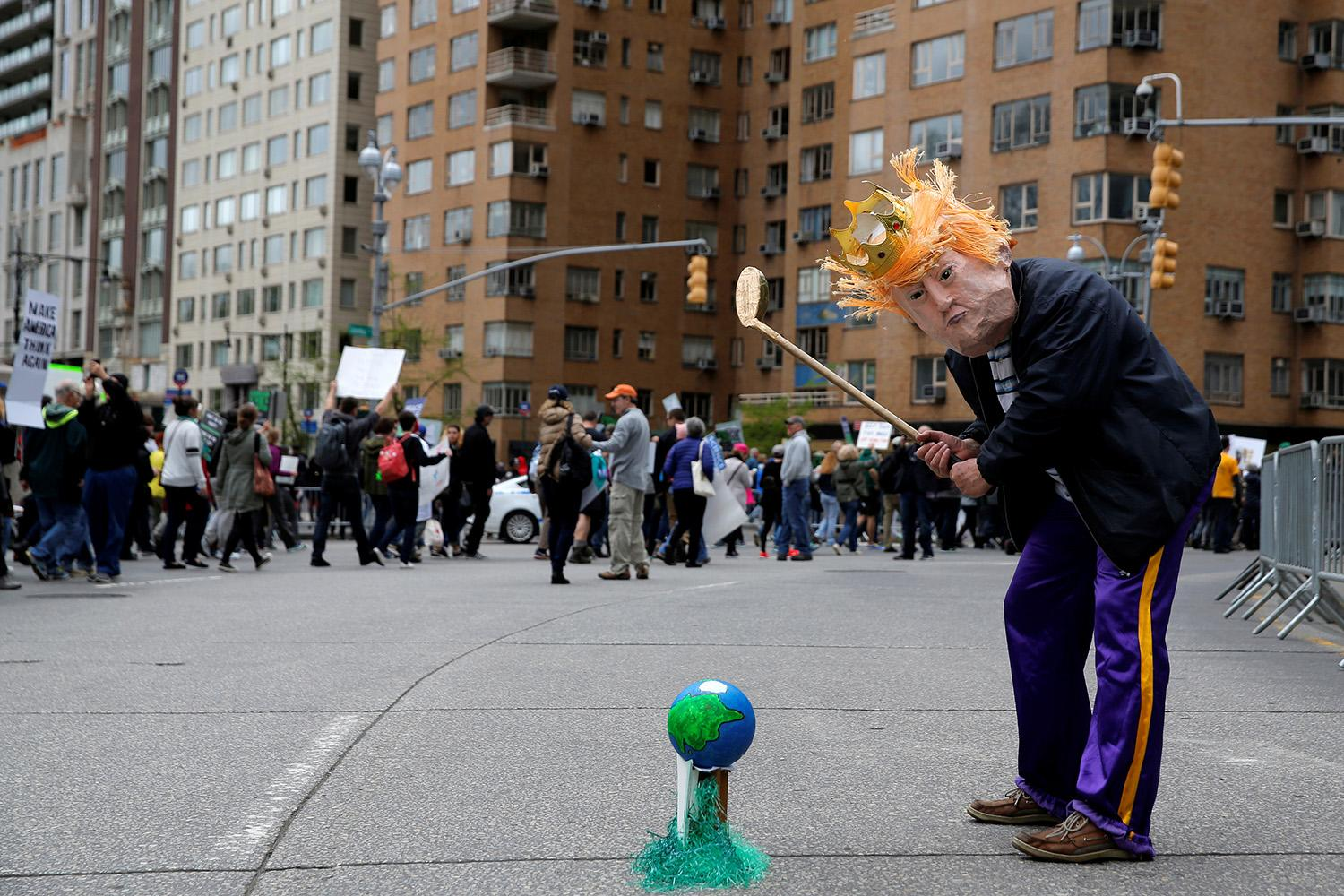 <p>A protester dressed as U.S. president Donald Trump pretends to play golf with the Earth during the Earth Day 'March For Science NYC' demonstration to coincide with similar marches globally in Manhattan, New York, April 22, 2017. (Andrew Kelly/Reuters) </p>