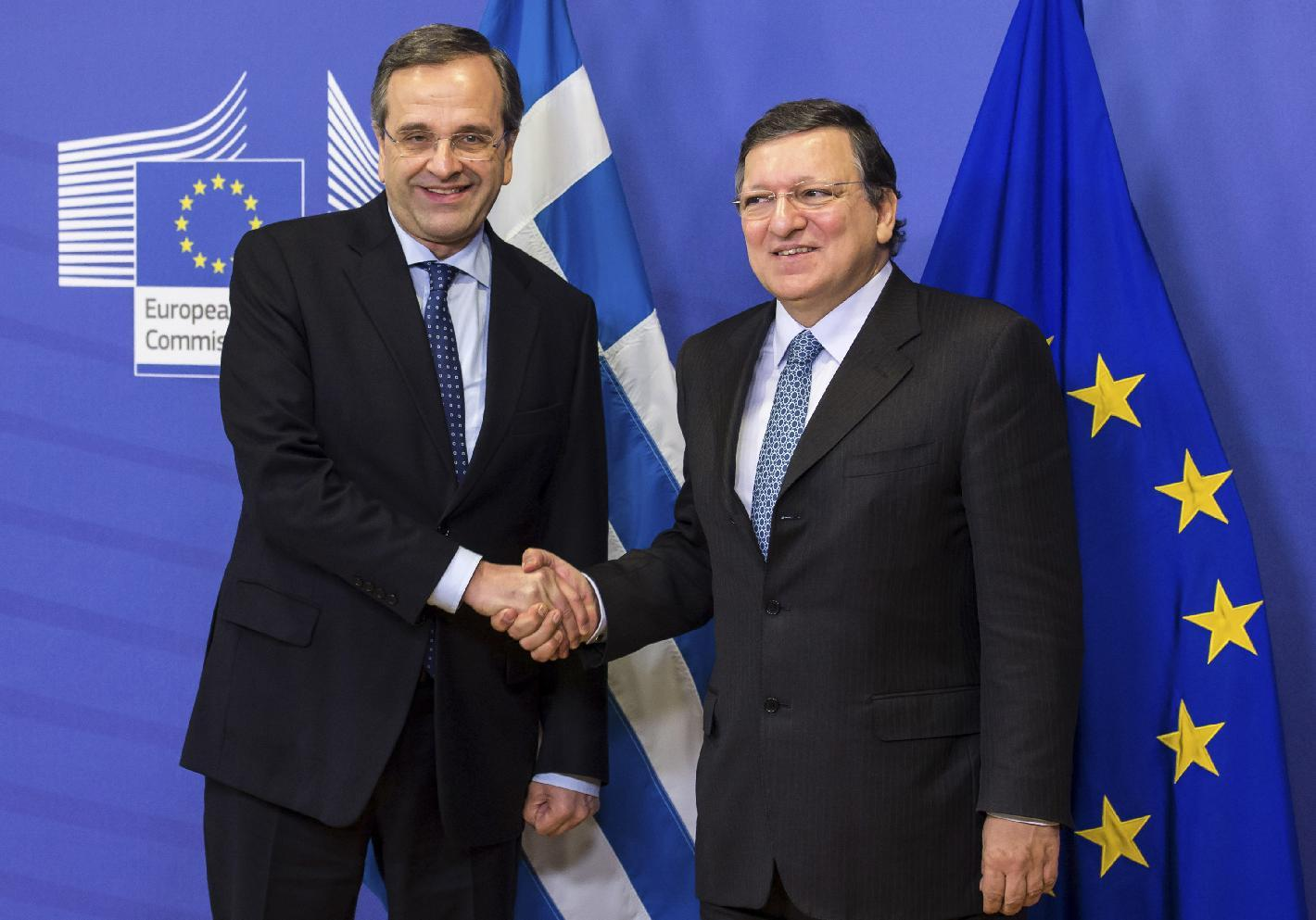 FILE - This is a Wednesday Dec. 4, 2013 file photo of European Commission President Jose Manuel Barroso, right, and Greek Prime Minister Antonis Samaras as they shake hands as they pose for photos upon arrival at the European Commission headquarters in Brussels. The European Union says Greece has reached a major financial milestone that was required if it were to be granted more debt relief. European Commission spokesman Simon O'Connor said Wednesday April 23, 2014 that Greece's government revenues last year exceeded expenditure when interest payment and other items were excluded. (AP Photo/Geert Vanden Wijngaert, File)