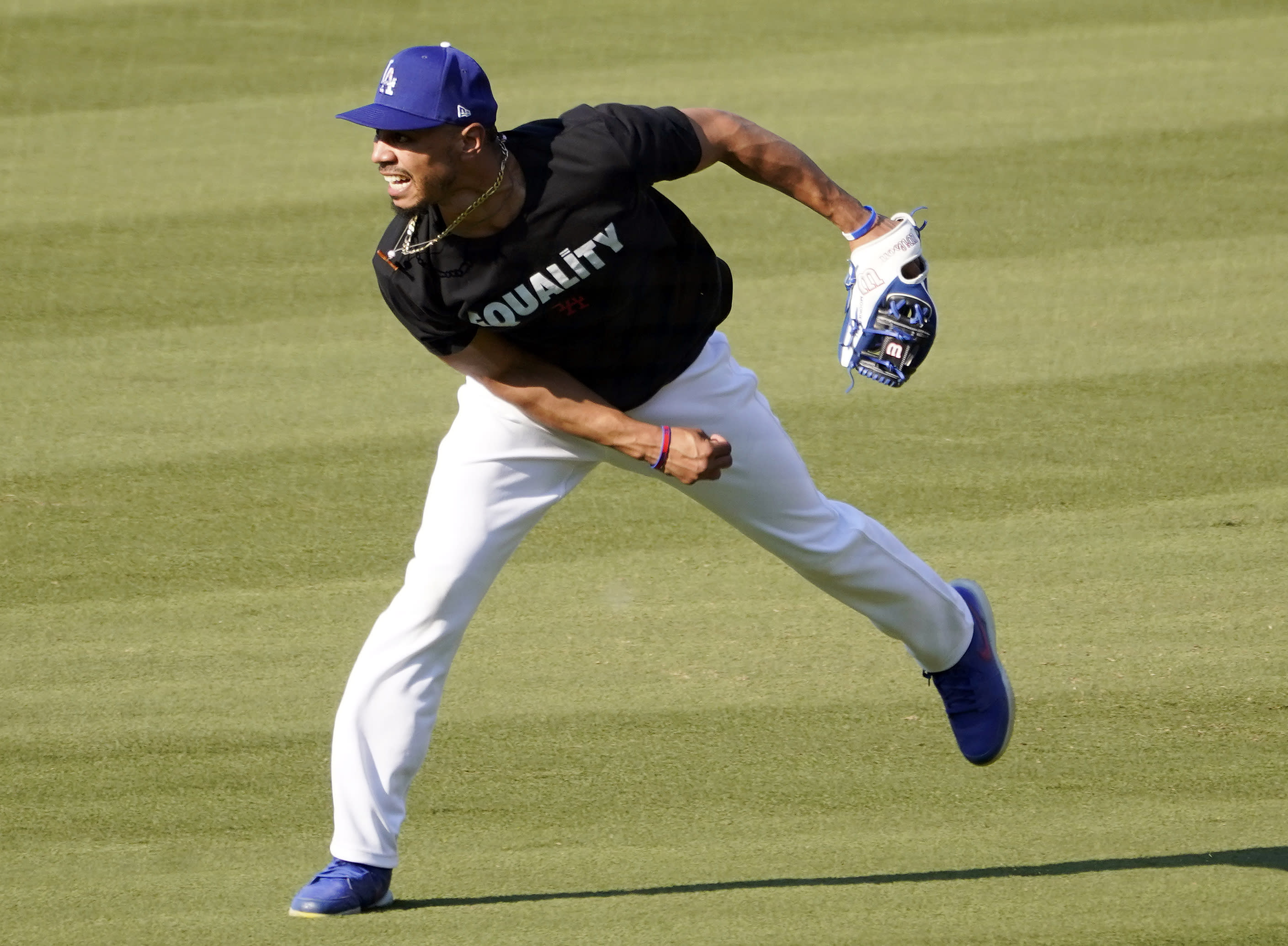 Los Angeles Dodgers' Mookie Betts follows through on a throw to the infield during a workout, Tuesday, Sept. 29, 2020, at Dodger Stadium in Los Angeles, ahead of Wednesday's Game 1 of a National League wild-card baseball series against the Milwaukee Brewers. (AP Photo/Chris Pizzello)
