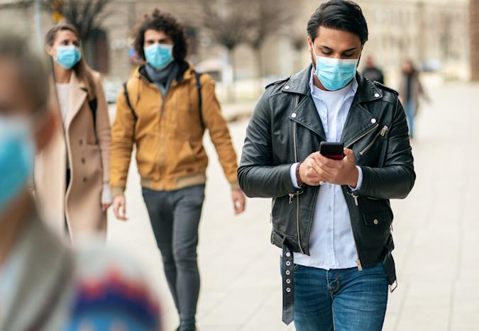 Portrait of young man on the street wearing face protective mask to prevent Coronavirus and anti-smog and using smartphone