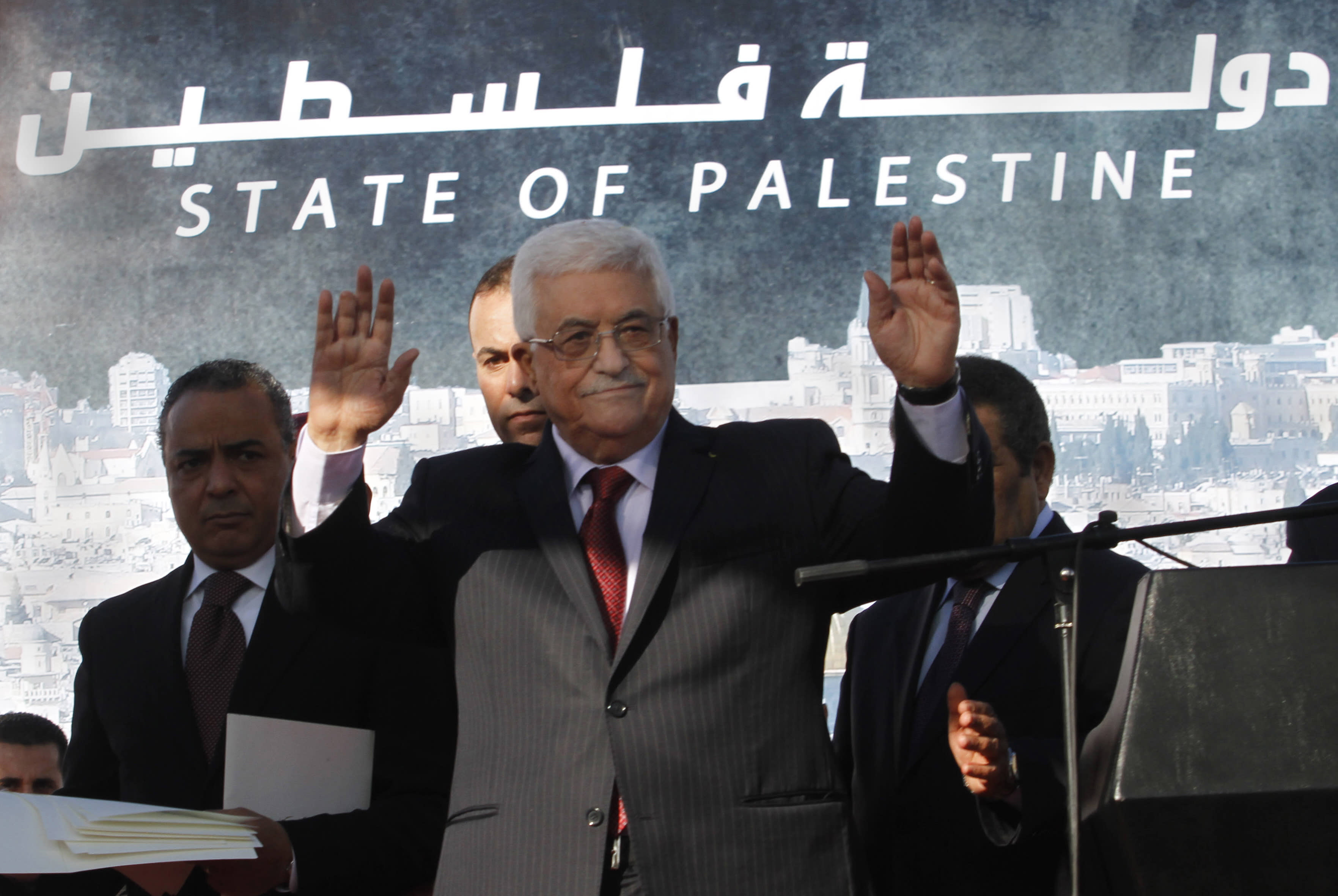 """FILE - In this Dec. 2, 2012 file photo, Palestinian President Mahmoud Abbas waves to the crowd during celebrations for their successful bid to win U.N. statehood recognition. Palestinian officials said Monday Jan. 7, 2013, they will not rush to issue new passports and ID cards with the emblem """"State of Palestine"""" to avoid confrontation with Israel. Last week, Palestinian President Mahmoud Abbas decreed that in official documents """"State of Palestine"""" must replace """"Palestinian Authority,"""" the name of his self-rule government. (AP Photo/Nasser Shiyoukhi, File)"""