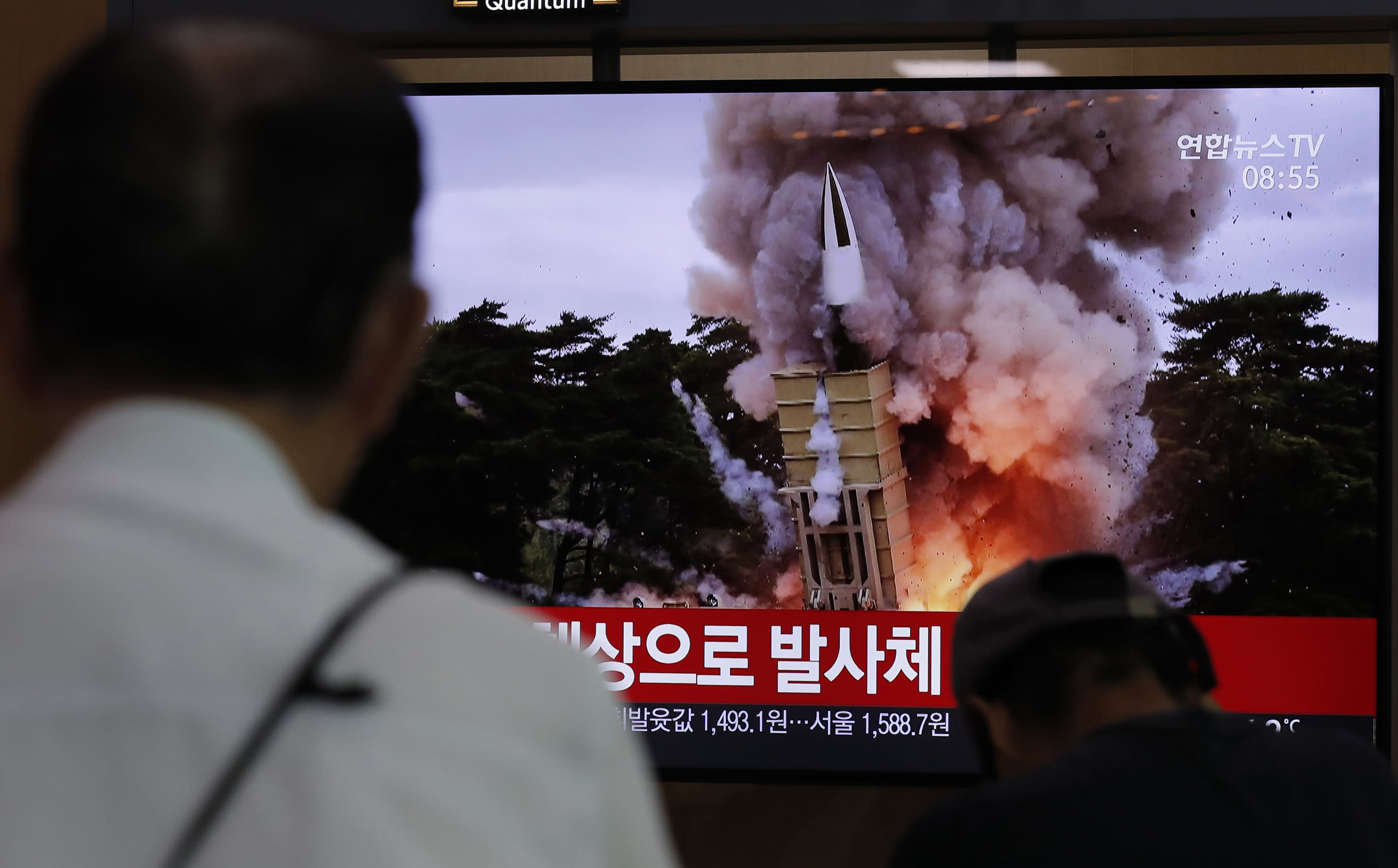 """People watch a TV news program reporting North Korea's firing projectiles with a file image at the Seoul Railway Station in Seoul, South Korea, Saturday, Aug. 24, 2019. North Korea fired two suspected short-range ballistic missiles off its east coast on Saturday in the seventh consecutive week of weapons tests, South Korea's military said, a day after it threatened to remain America's biggest threat in protest of U.S.-led sanctions on the country. The part of Korean letters read: """"Projectiles."""" (AP Photo/Lee Jin-man)"""
