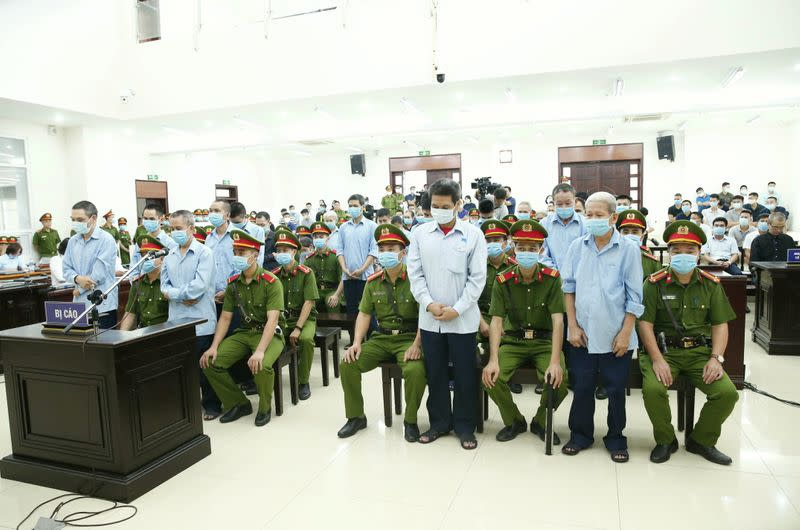 Farmers of Dong Tam village stand between police during court verdict in Hanoi