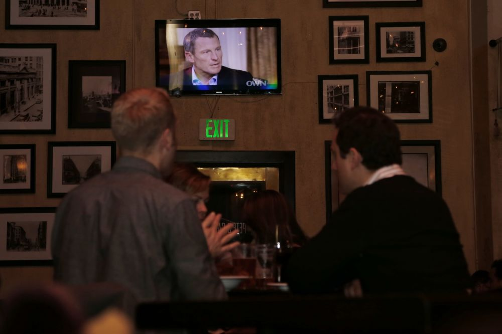The second night of Oprah Winfrey's interview of former cycling star Lance Armstrong is shown on video screens at Pete's Cafe Bar in downtown Los Angeles Friday,  Jan. 18, 2013. Through a marathon mea culpa that spanned two nights on TV, Armstrong spoke almost dispassionately about lying and cheating, about arrogance and bullying, about lost honor, status, achievement and income.(AP Photo/Reed Saxon)