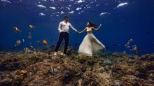 Bride and groom pose for extravagant underwater wedding shoot