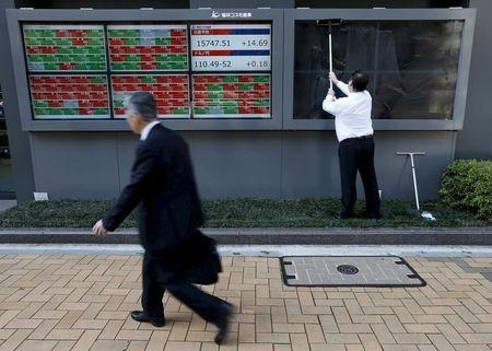 File photo of a man cleaning electronic boards outside a brokerage in Tokyo