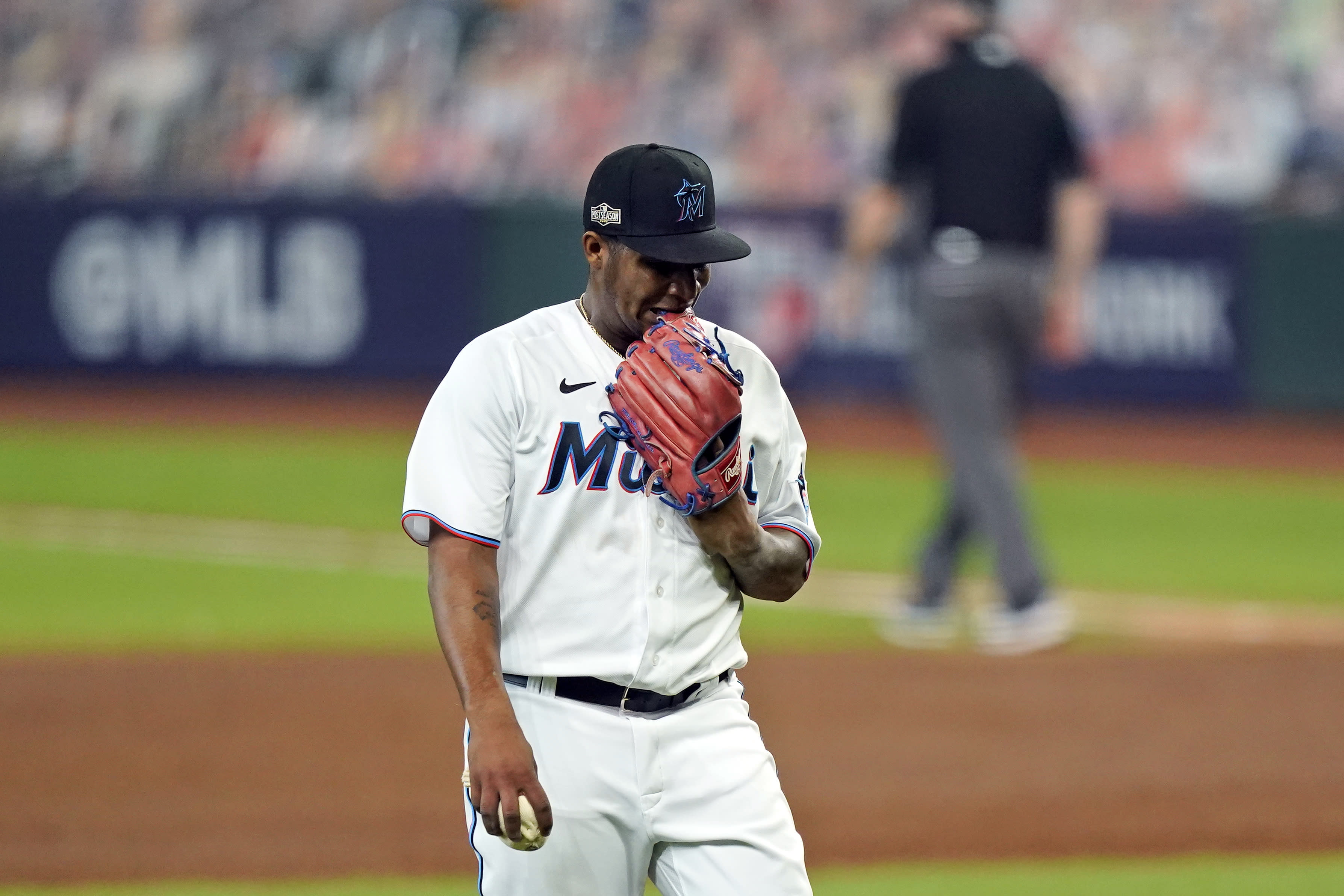 Miami Marlins starting pitcher Sixto Sanchez bites his glove as he walks off they field after the final out in the third inning in Game 3 of a baseball National League Division Series against the Atlanta Braves, Thursday, Oct. 8, 2020, in Houston. (AP Photo/David J. Phillip)