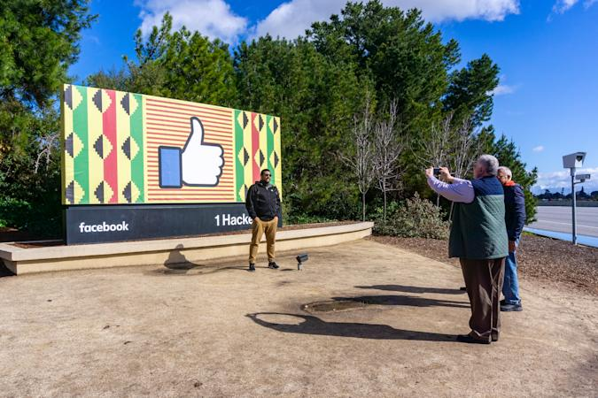 February 10, 2019 Menlo Park / CA / USA - Group of people taking photos with the Facebook logo (customized for black history month) located outside the Company's main campus in Silicon Valley;