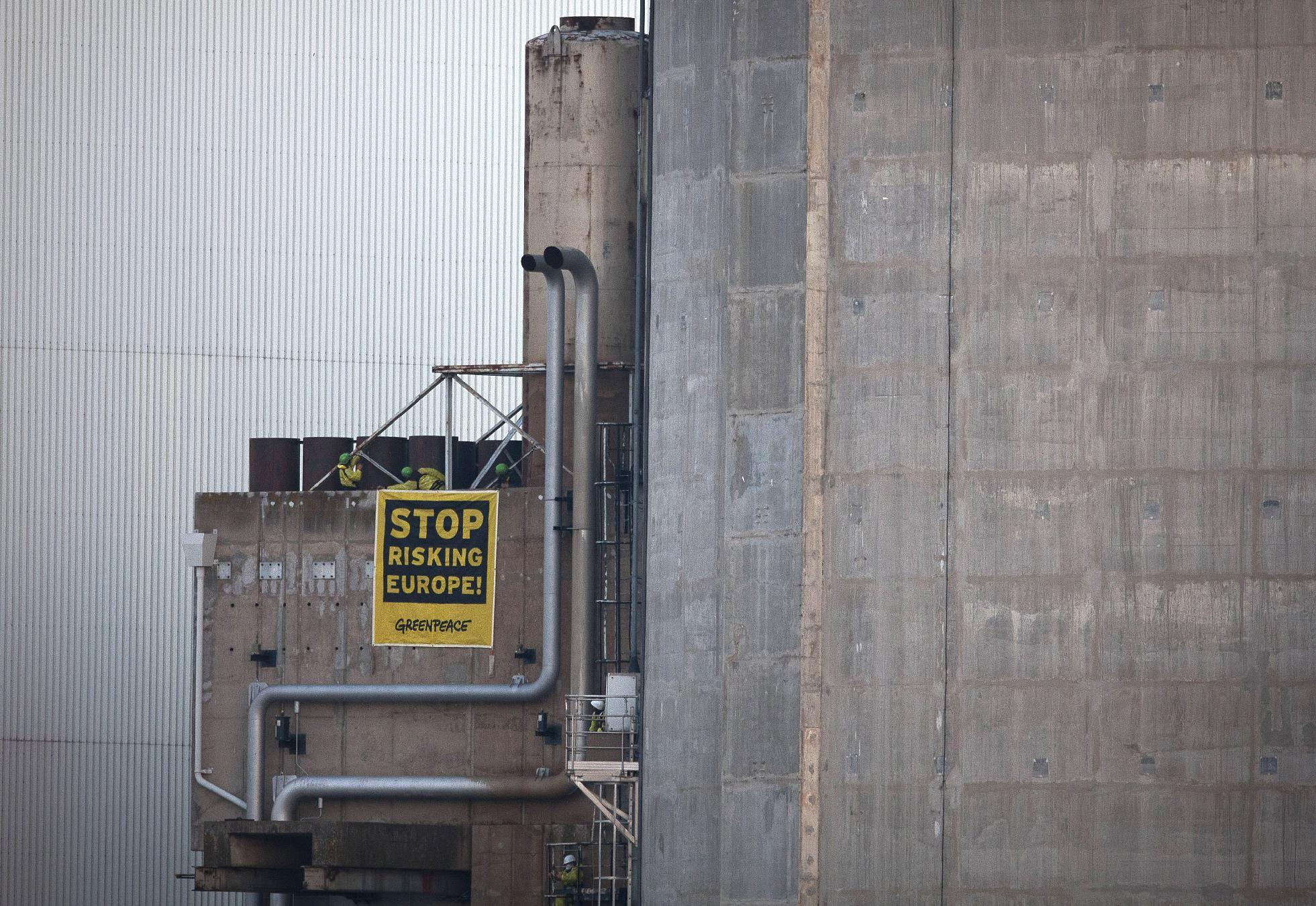 "In this photo provided by environmental group Greenpeace, activisits hang a banner reading ""Stop Risking Europe"" next to one of the reactors at the Fessenheim nuclear power plant, eastern France, Tuesday, March 18, 2014. More than 60 Greenpeace activists have occupied a nuclear plant in eastern France to protest the nation's reliance on atomic power. In a statement Greenpeace France said the activists had come from 14 countries across Europe ""to denounce the risk to Europe from France's nuclear power,"" and to promote a transition to other energy sources. (AP Photo/Greenpeace, Daniel Mueller)"