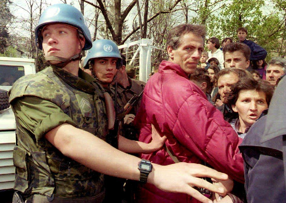 Danish UN soldiers push Bosnians away, many of them refugees from Gorazde seeking safety at the UN headquarters in Sarajevo in April 1994 (AFP Photo/Anja Niedringhaus)