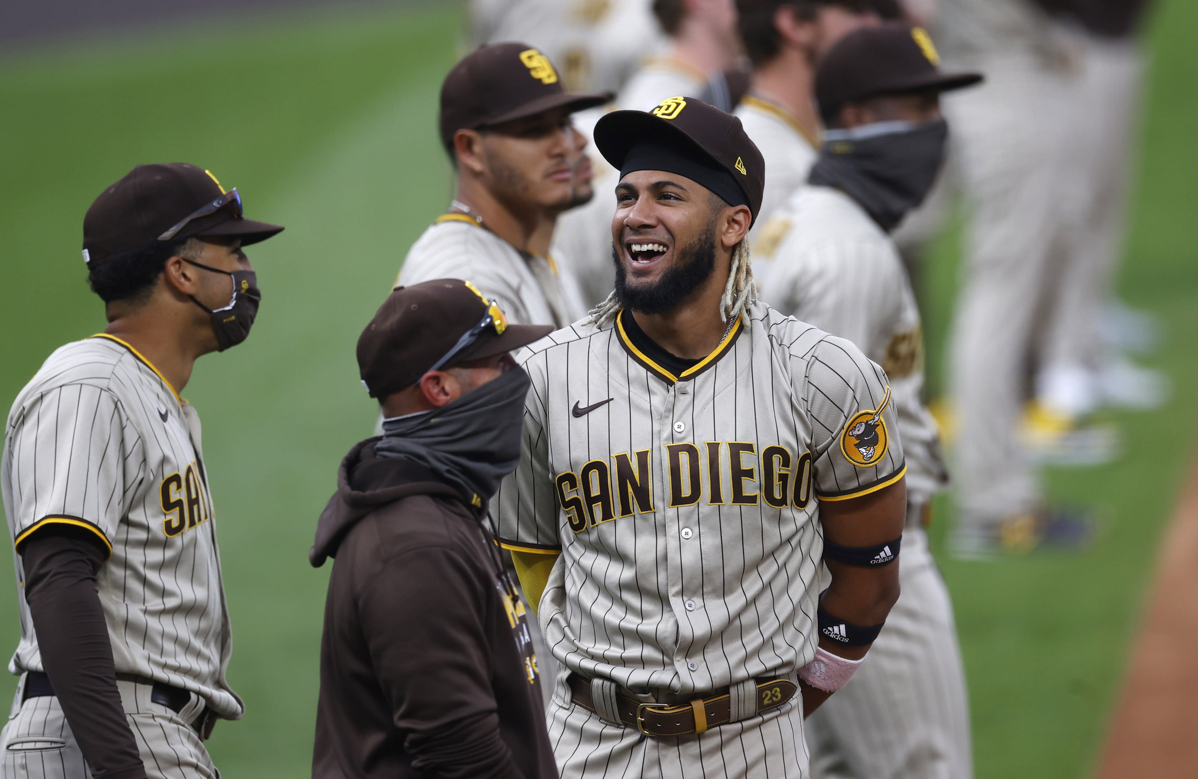 San Diego Padres shortstop Fernando Tatis Jr. jokes with teammates as they line up for introductions before a baseball game against the Colorado Rockies Friday, July 31, 2020, in Denver. (AP Photo/David Zalubowski)