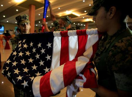 Members of the U.S. Marine corps roll the American flag after the Philippines-US amphibious landing exercise (PHIBLEX) closing ceremony inside the Philippine Marines headquarters in Taguig city, metro Manila, Philippines October 11, 2016. REUTERS/Romeo Ranoco/File Photo