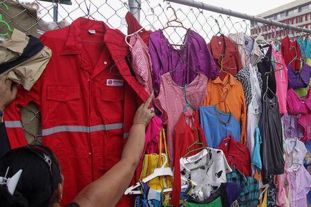 A customer looks at a PDVSA's overalls for sale at a market in Maracaibo, Venezuela September 11, 2016. REUTERS/Jesus Contreras