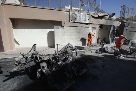 Cleaning workers clear debris at the scene of a car bomb explosion near the United Arab Emirates embassy in the Libyan capital of Tripoli November 13, 2014. REUTERS/Ismail Zitouny