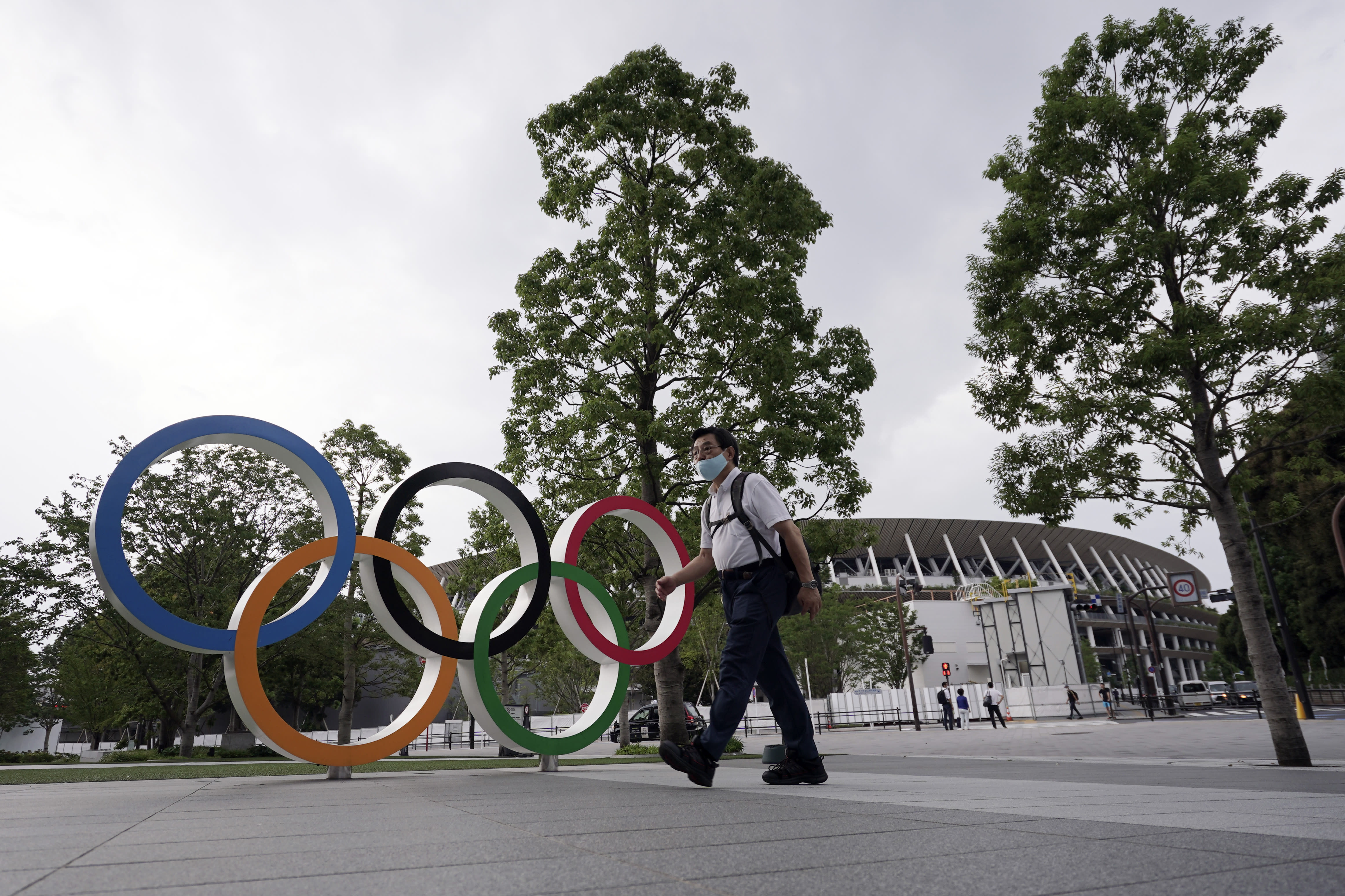 A man wearing a mask against the spread of the new coronavirus walks at the Olympic rings in front of the New National Stadium Wednesday, July 22, 2020, in Tokyo. The postponed Tokyo Olympics have again reached the one-year-to-go mark. But the celebration is small this time with more questions than answers about how the Olympics can happen in the middle of a pandemic. That was before COVID-19 postponed the Olympics and pushed back the opening to July 23, 2021. (AP Photo/Eugene Hoshiko)
