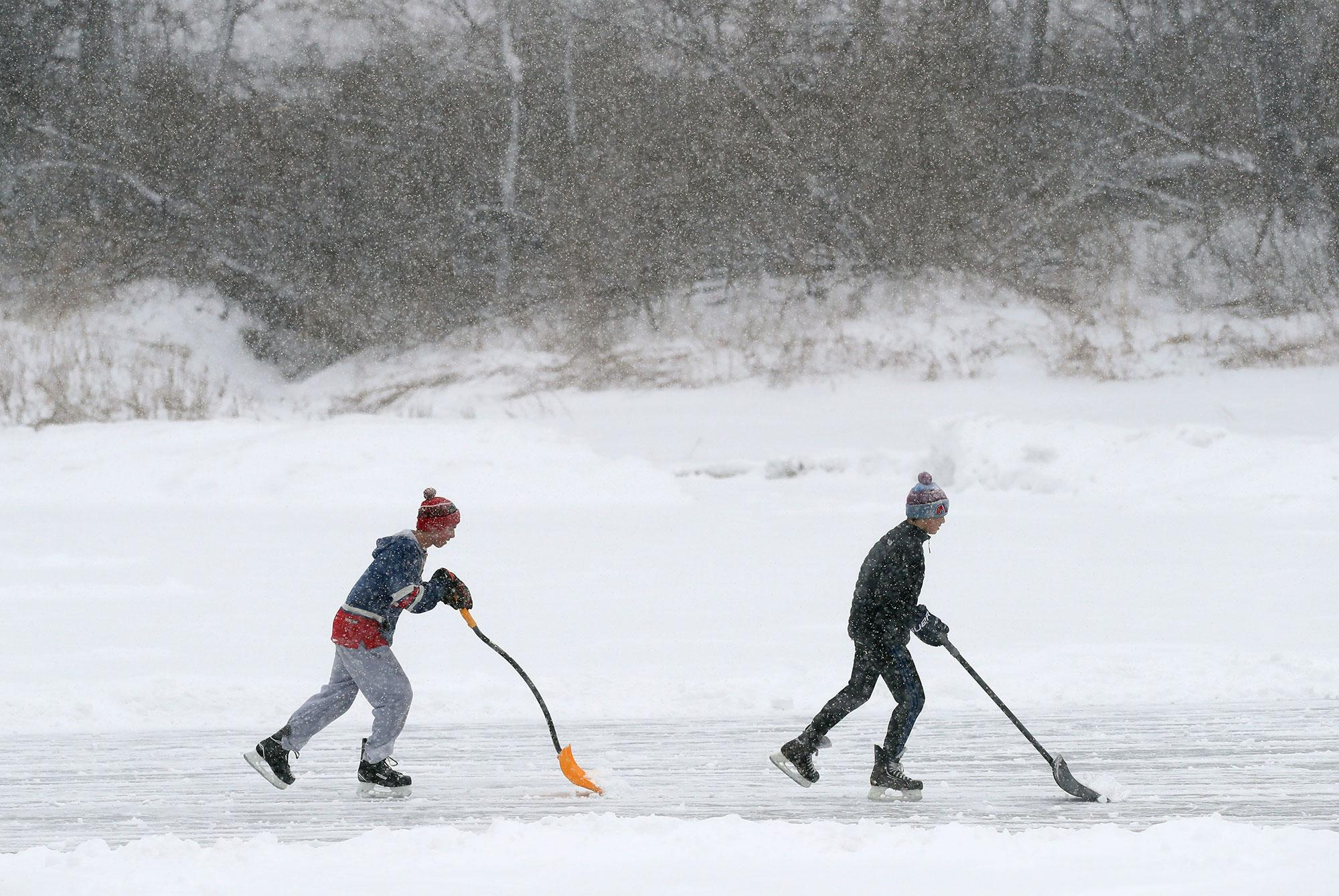 <p>Pond hockey players attempt to shovel snow faster than it can fall during a storm, Tuesday, March 14, 2017, in Yarmouth, Maine. About one foot of snow is expected in the area. A blustery late-season storm is hitting the Northeast, closing schools and prompting dire warnings to stay off the roads. (AP Photo/Robert F. Bukaty) </p>