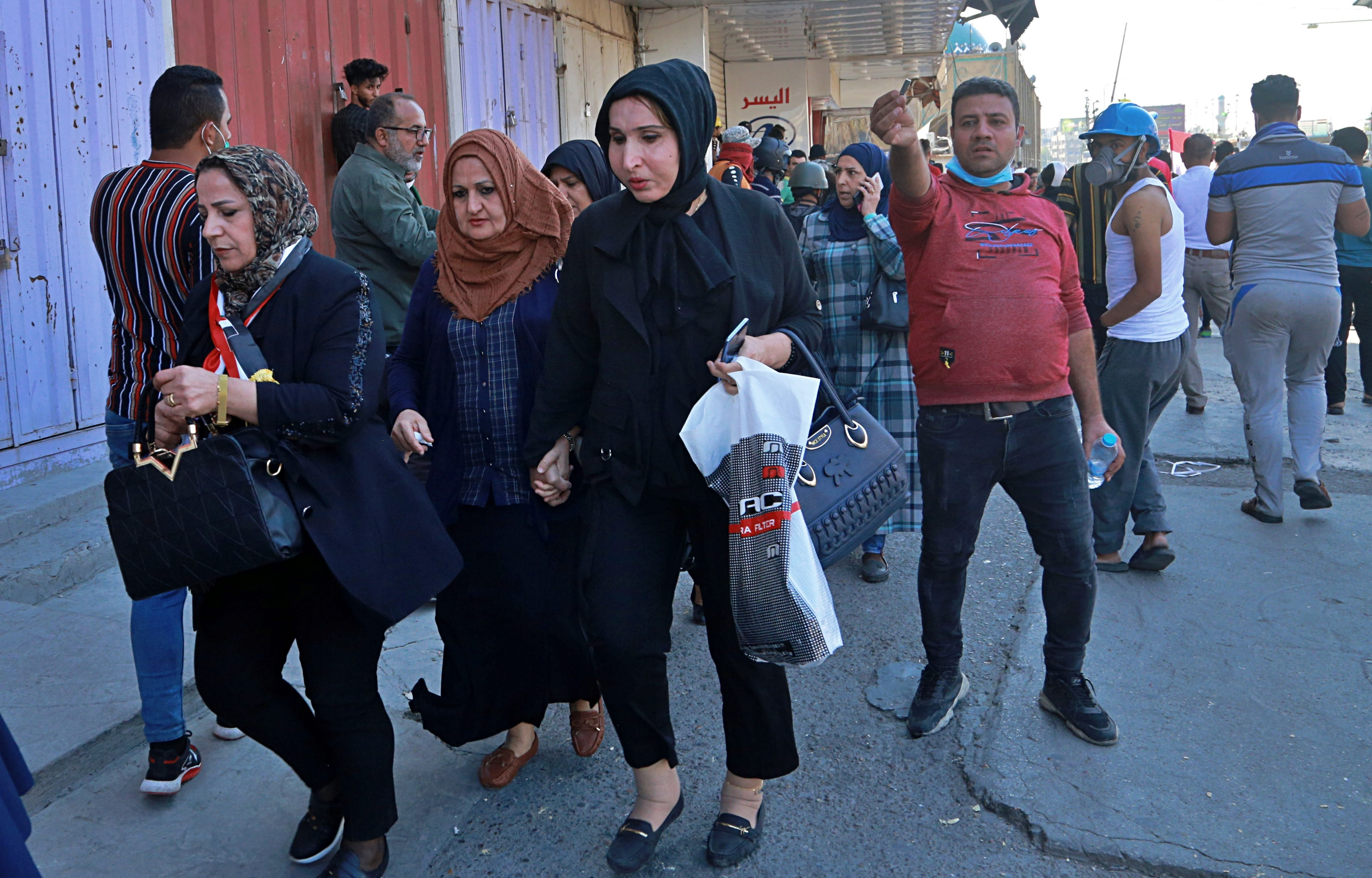 Employees of the central bank leave their workplaces in central Baghdad, Iraq, Wednesday, Nov. 6, 2019. Iraqi security forces deployed in large numbers around the bank and began evacuating employees from the building. The protesters did not appear to be heading toward the bank itself. (AP Photo/Hadi Mizban)