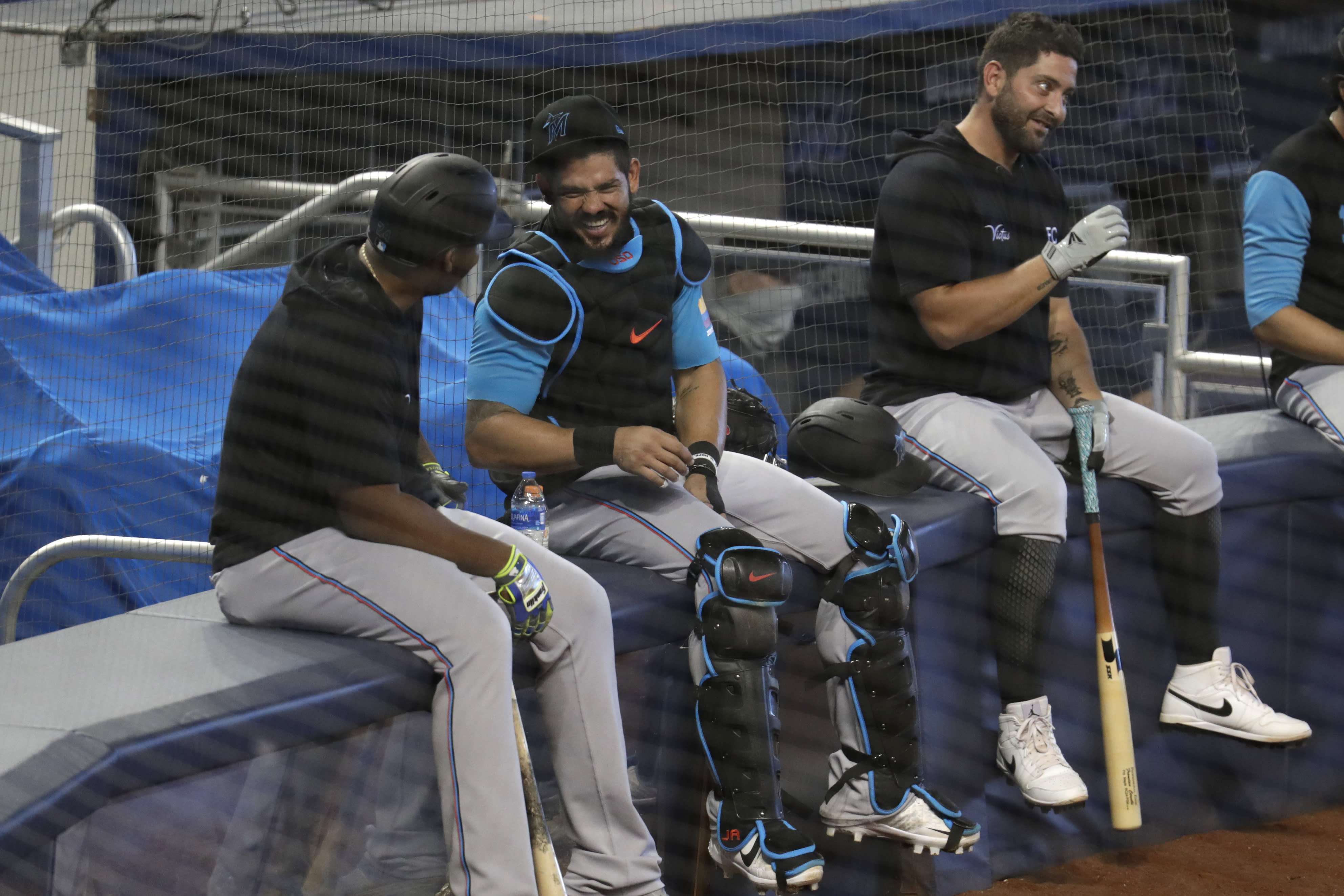 Miami Marlins catchers Jorge Alfaro, center, and Francisco Cervelli, right, pause during baseball practice at Marlins Park, Wednesday, July 8, 2020, in Miami. (AP Photo/Lynne Sladky)