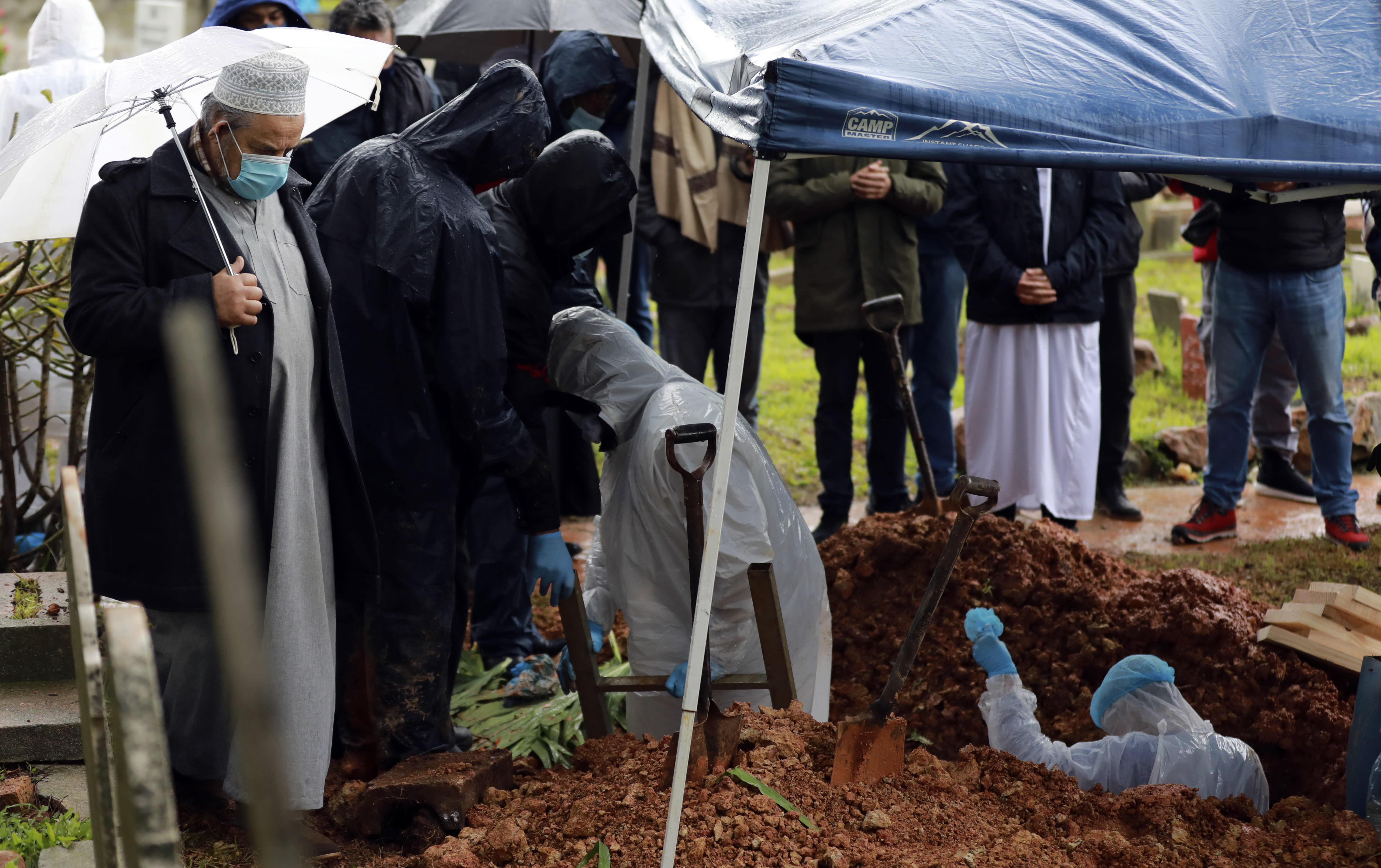 Undertakers wearing personal protective equipment exit the grave of Shaykh Seraj Hassan Hendricks during the funeral at the Mowbray cemetery in Cape Town, South Africa, Friday July 10, 2020. Hendricks who died of COVID-19 was the resident sheikh at the Azzawia Institute. (AP Photo/Nardus Engelbrecht)