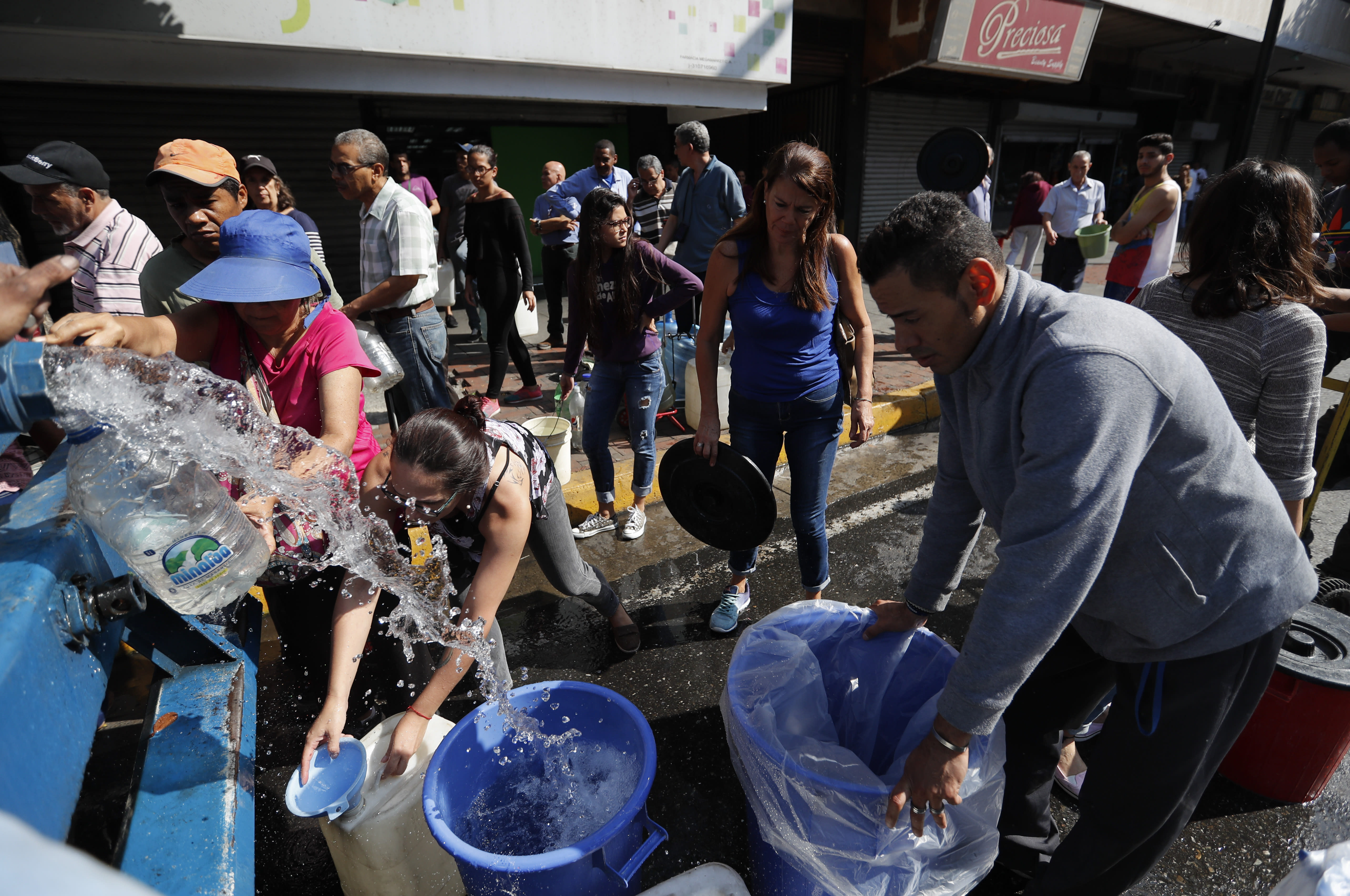 People collect water from a truck that delivers water during rolling blackouts, in Caracas, Venezuela, Tuesday, March 12, 2019. The blackout marked another harsh blow to a country paralyzed by turmoil as the power struggle between Venezuelan President Nicolas Maduro and opposition leader Juan Guaido stretches into its second month and economic hardship grows. (AP Photo/Eduardo Verdugo)
