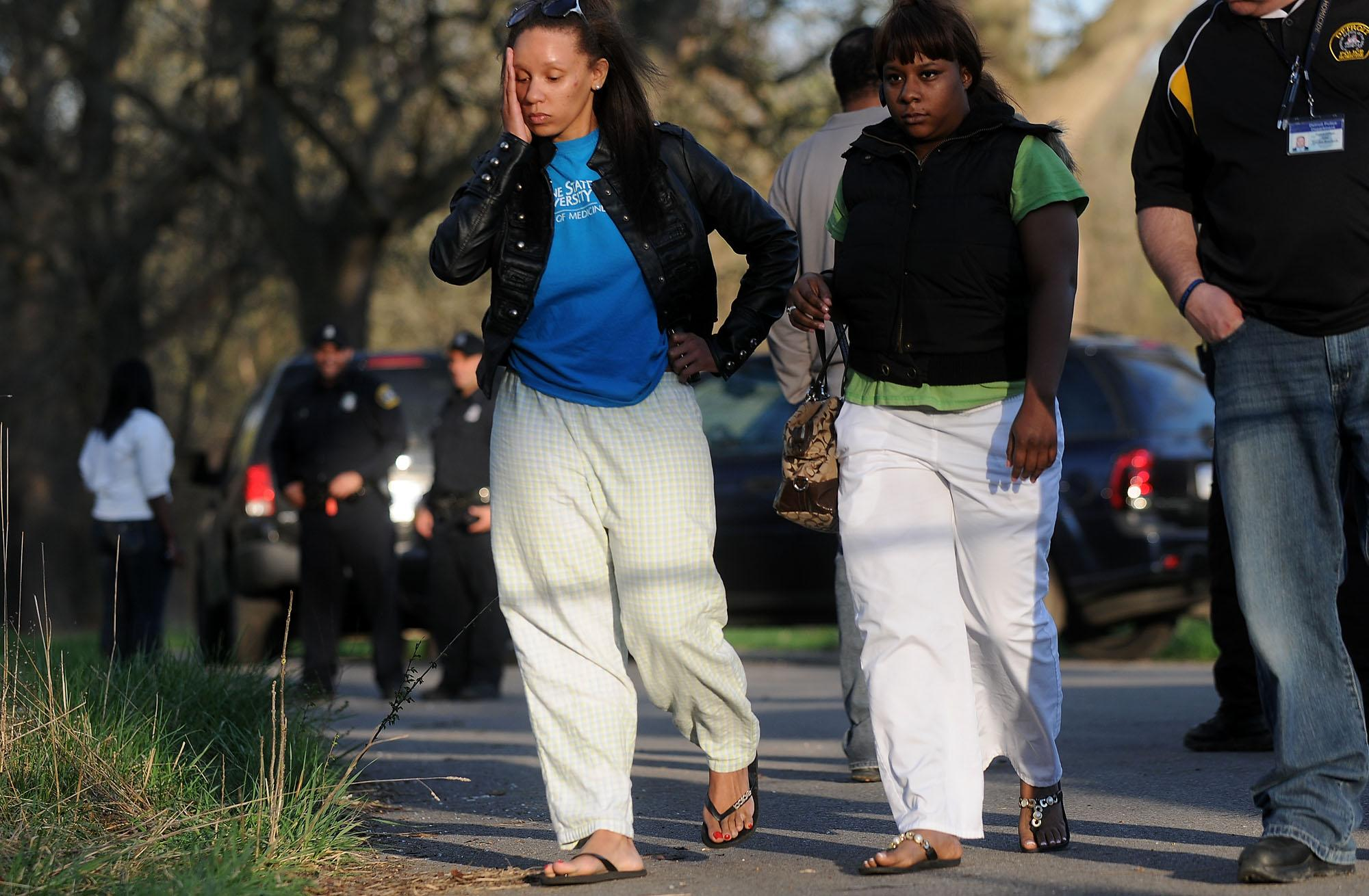 Krystal Brown, left, cousin of Abreeya Brown, leaves the scene where to bodies of two women were found after talking with police, with another relative of the missing Abreeya Brown, Sunday, March 25, 2012. The bodies are likely the remains of two housemates, Abreeya Brown, 18, and Ashley Conaway, 21, who witnesses claim were forced into a car trunk at gunpoint nearly a month ago, police said. (AP Photo/The Detroit News, Elizabeth Conley) DETROIT FREE PRESS OUT; HUFFINGTON POST OUT