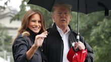 Melania Trump smiles and holds hands with the president to visit Florida hurricane victims